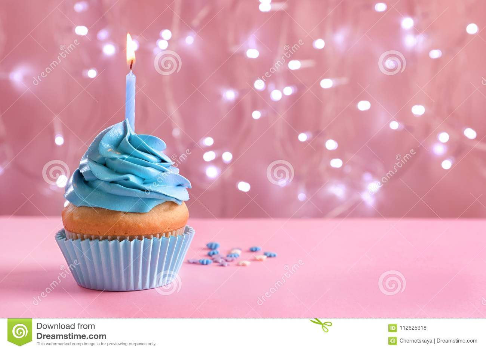 与灼烧的蜡烛的生日杯形蛋糕在桌上