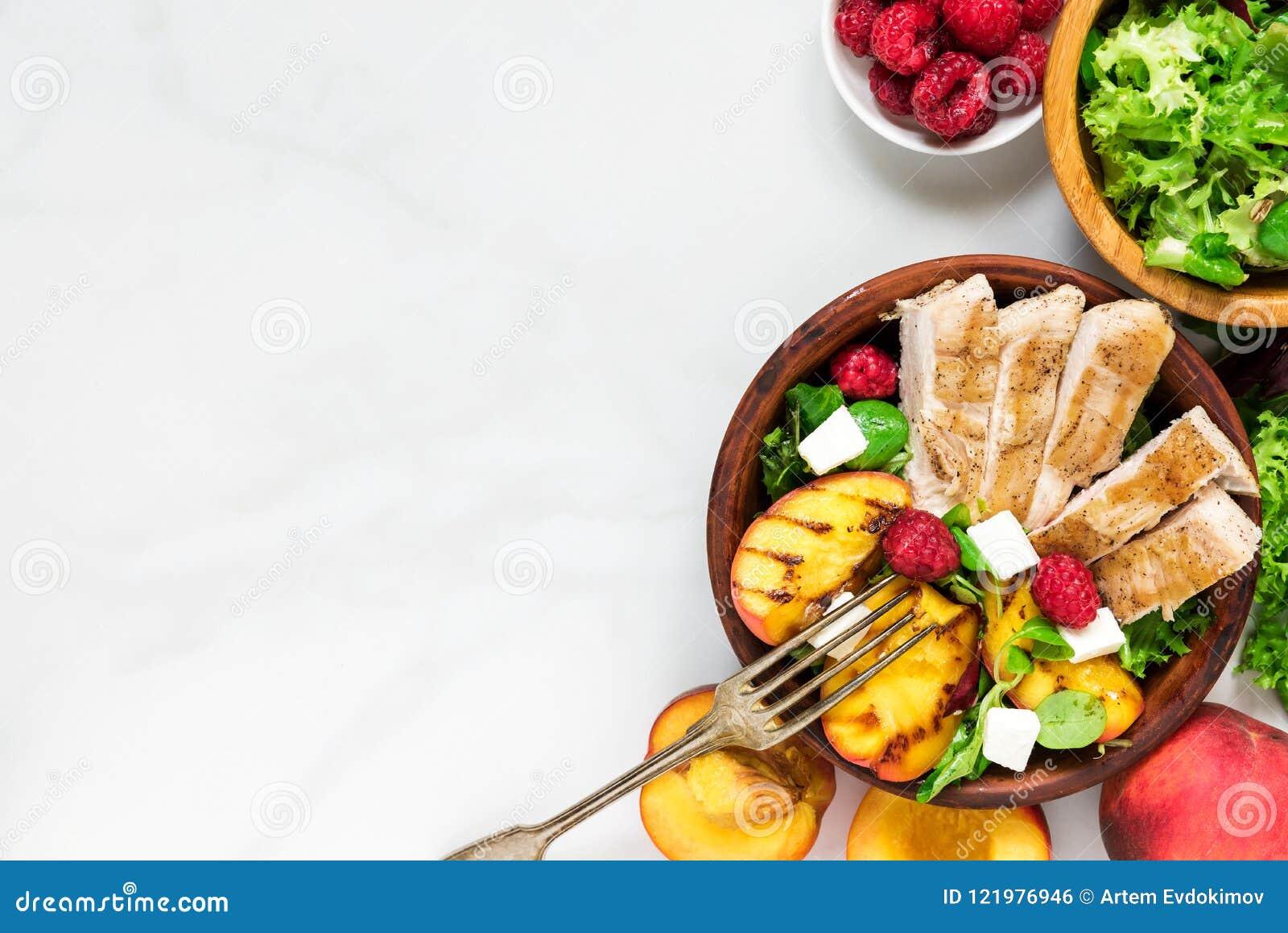 与烤鸡的夏天沙拉和桃子、希腊白软干酪和莓在一个碗有叉子的 健康的食物 顶视图