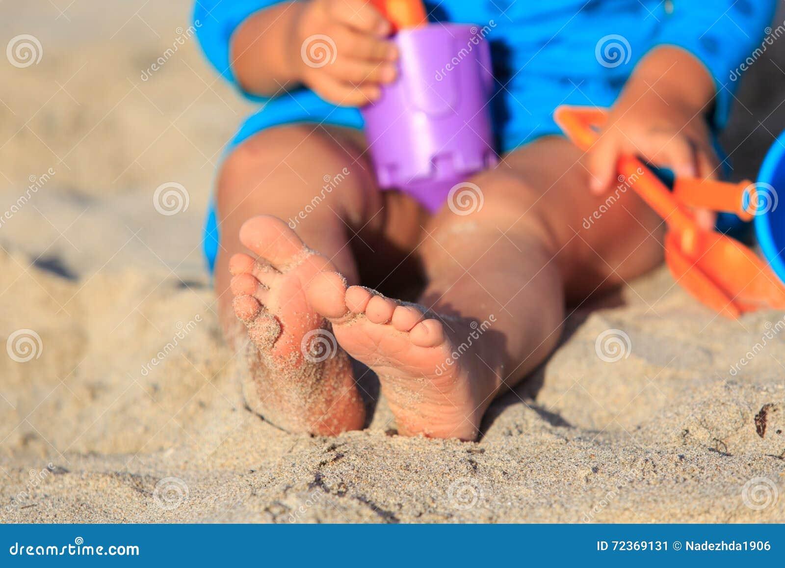 与玩具的小女孩戏剧在海滩
