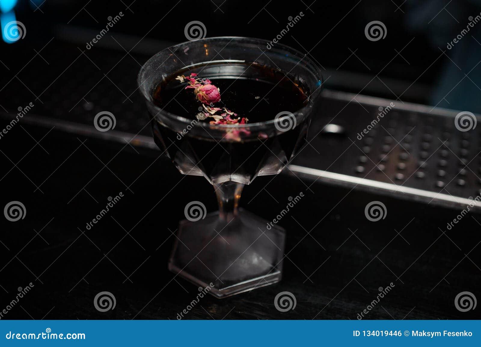 与用玫瑰花瓣装饰的酒精饮料的鸡尾酒杯