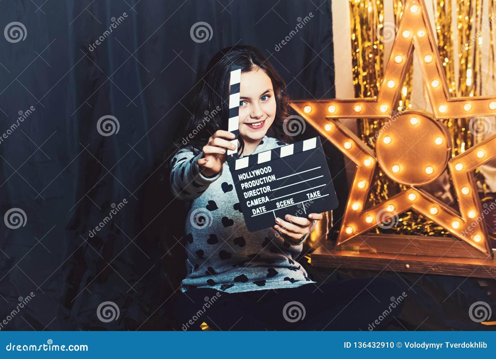 与电影拍板或clapperboard的愉快的儿童游戏 女孩微笑在金黄星的电影厂与电灯泡