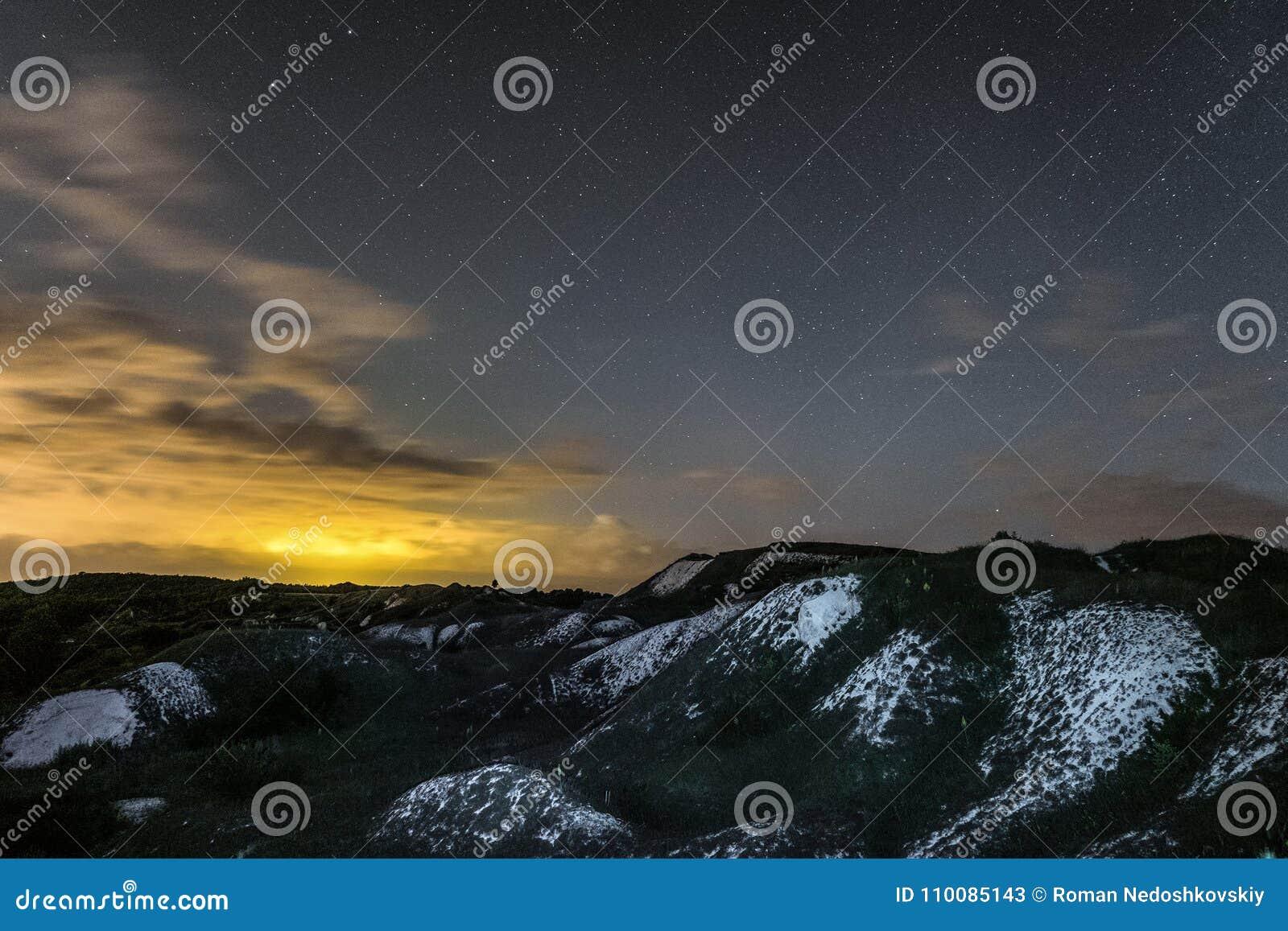 与白垩土坎的夜风景在多云和满天星斗的天空下
