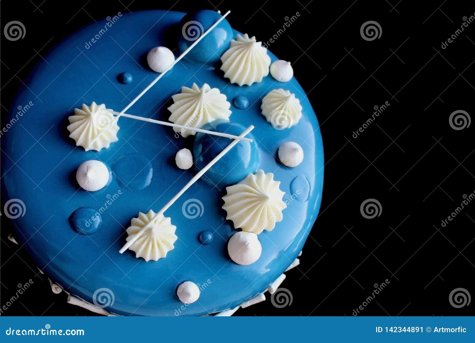 与白色巧克力ganache的蓝色发光的蛋糕和在黑背景隔绝的镜子釉