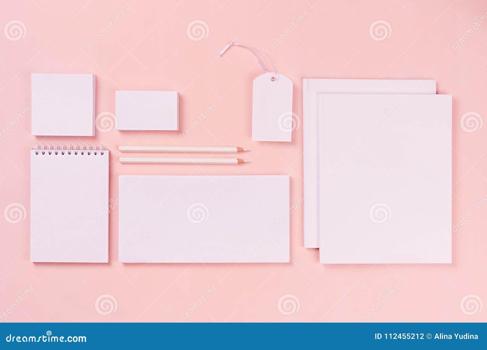 与白色空白的文具的现代minimalistic工作区在软的粉红彩笔背景,顶视图