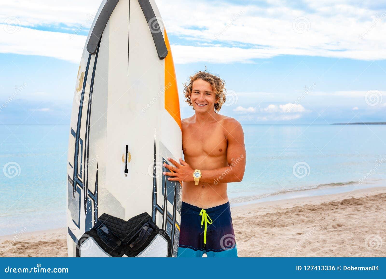 与白色空白的水橇板的英俊的人步行等待波浪冲浪斑点在海海洋岸 体育的概念