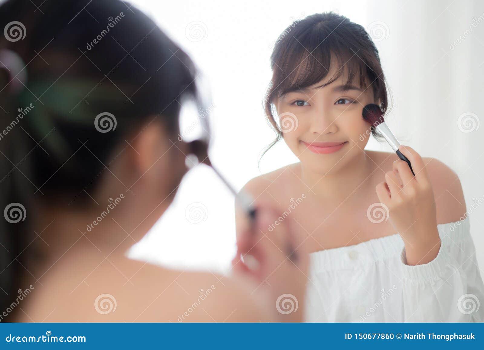 与看镜子的面孔的秀丽画象年轻亚洲妇女微笑申请与刷子面颊的构成在卧室