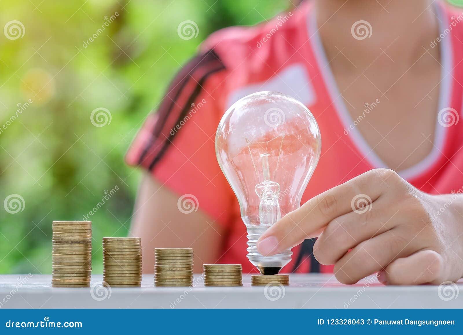 与硬币堆的电灯泡在木桌上早晨 能量和节约金钱,认为和财政概念