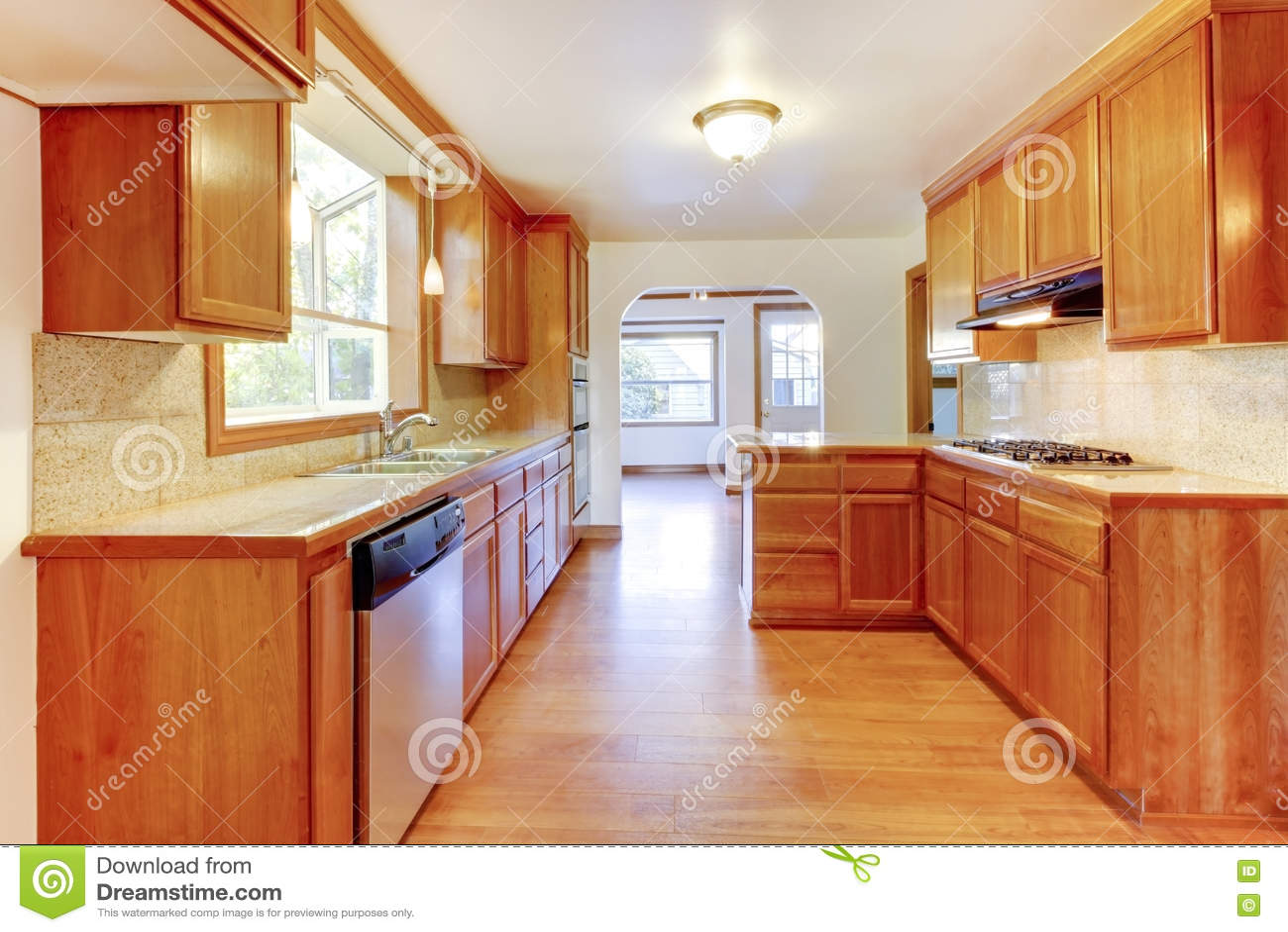 与硬木地板和白色ceili的晴朗的棕色厨房内部