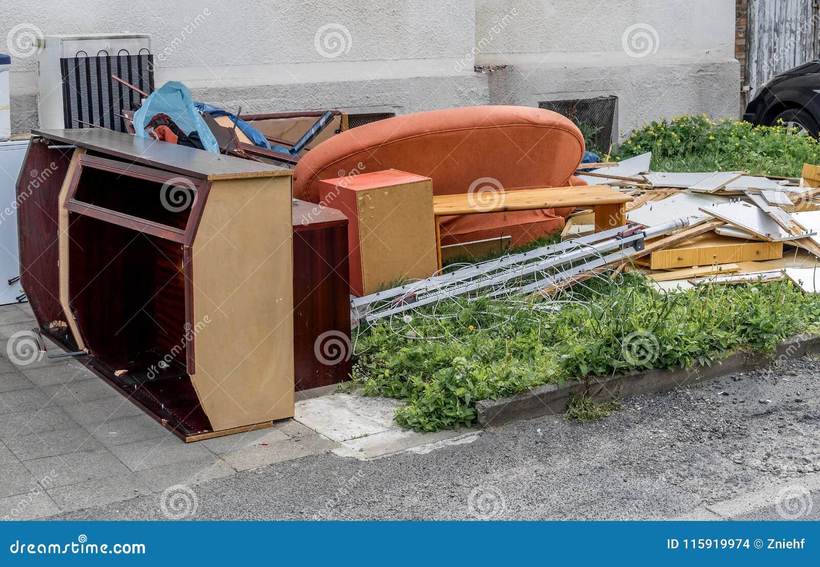 与碗柜、一个沙发和家具的庞大的废物在公寓前面的草坪
