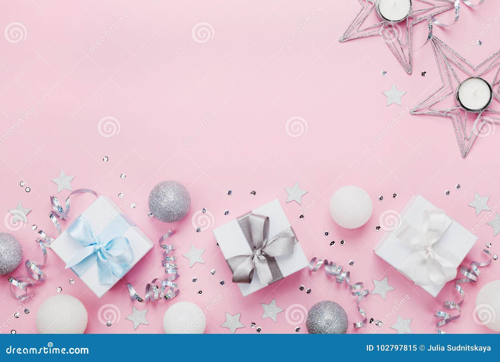 与礼物盒、球、装饰和衣服饰物之小金属片的圣诞节边界在桃红色台式视图 平的位置 复制贺卡的空间