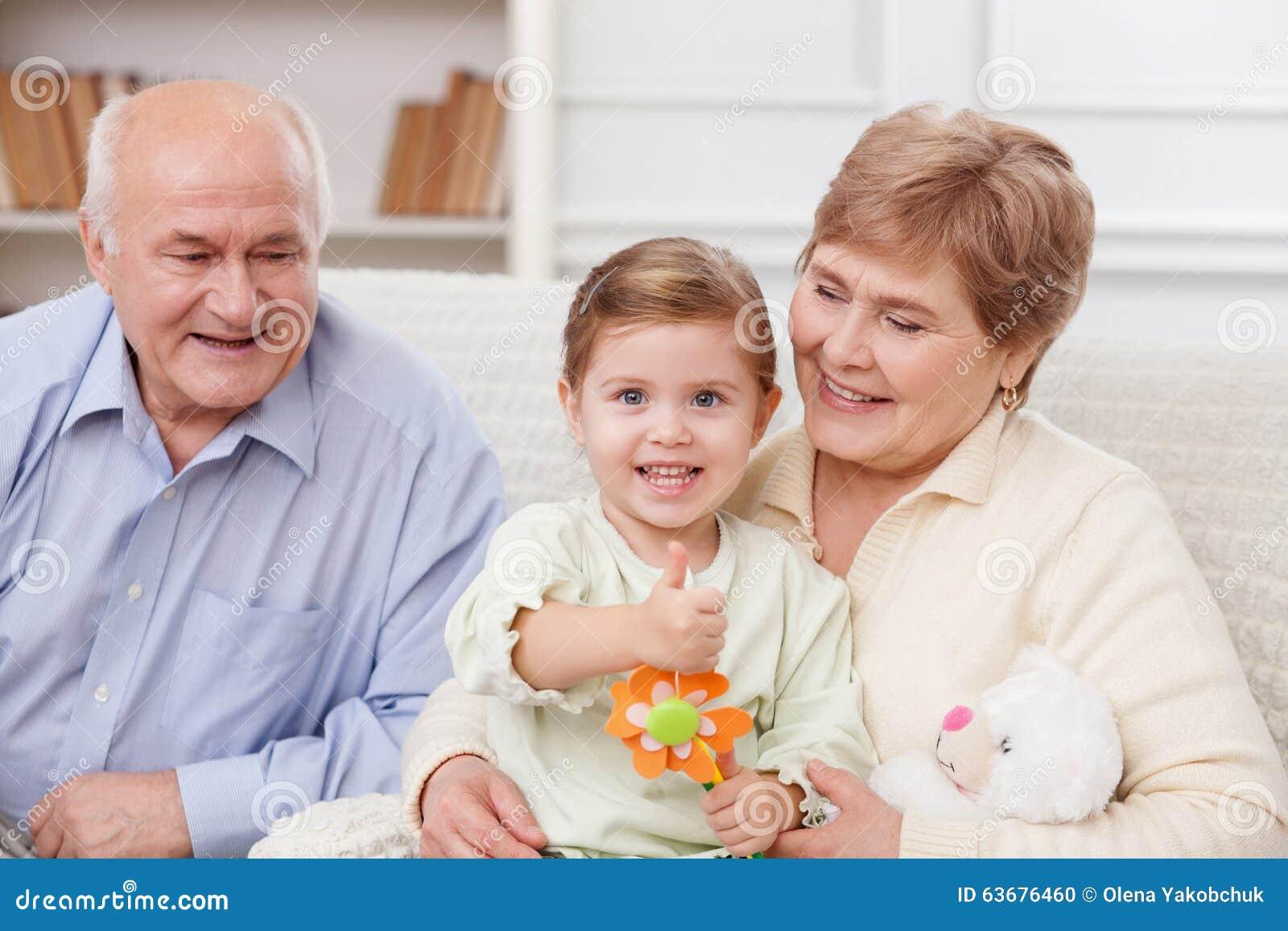与祖父母的俏丽的孩子打手势