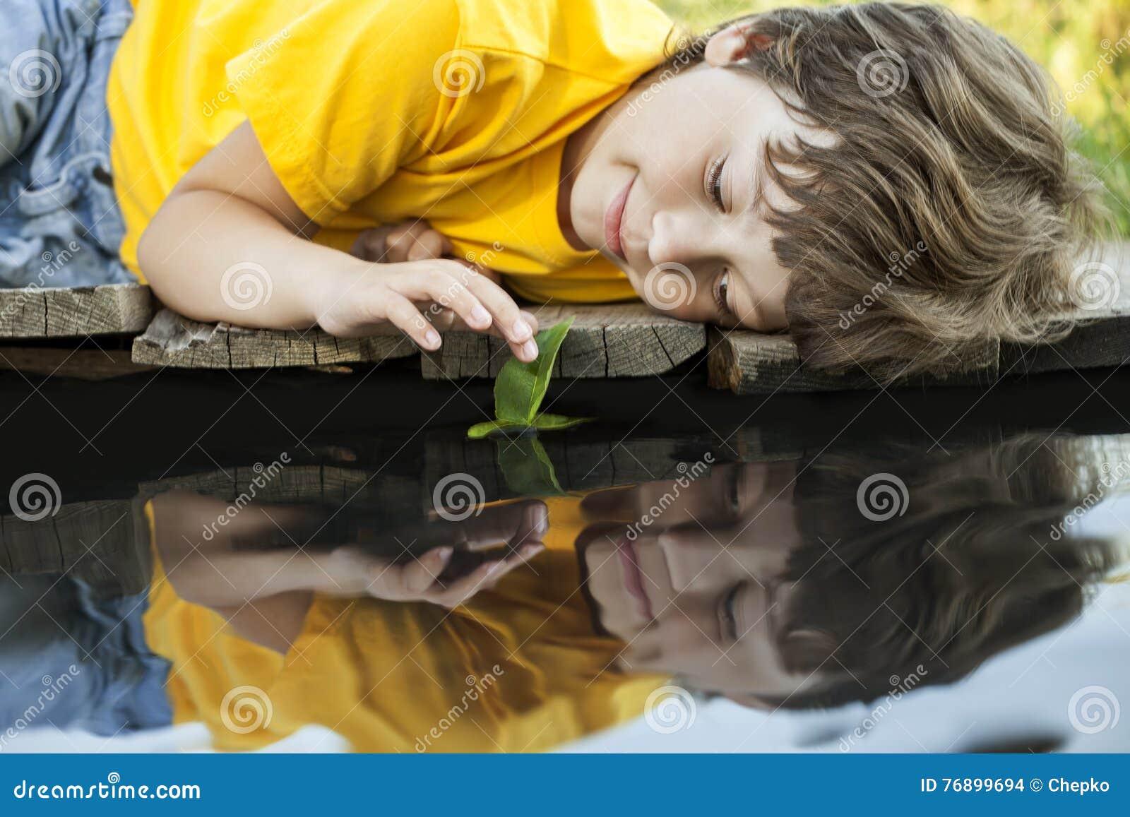 与秋天叶子船的男孩戏剧在水,孩子中在公园演奏w