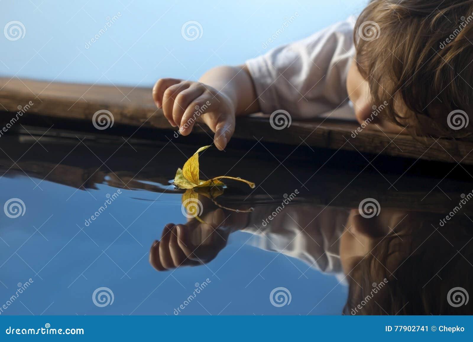 与秋天叶子船的男孩戏剧在水,孩子中在公园演奏wi