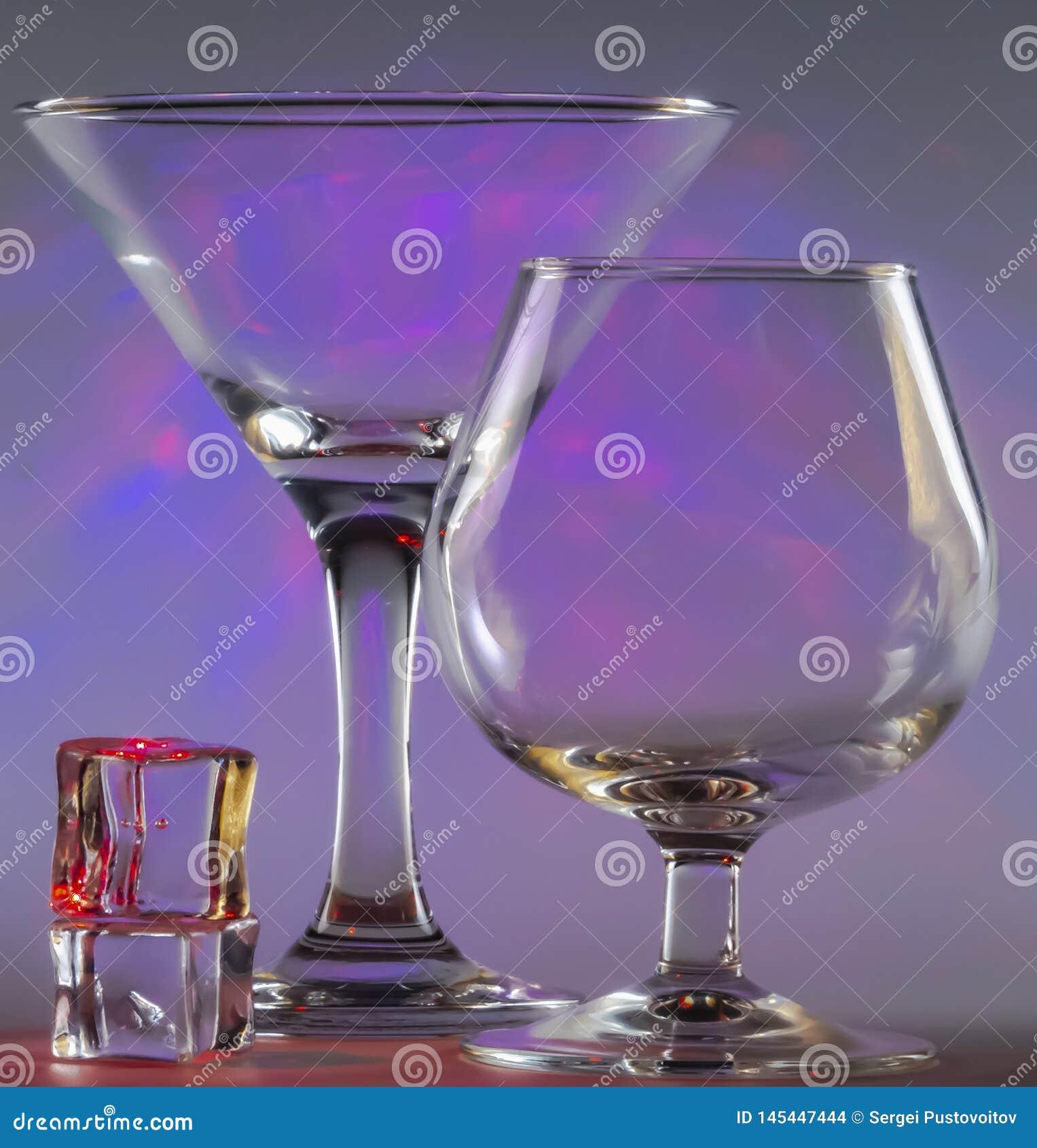 与科涅克白兰地玻璃和冰块一起的马蒂尼鸡尾酒玻璃与在背景的闪动的光滑的紫罗兰色光