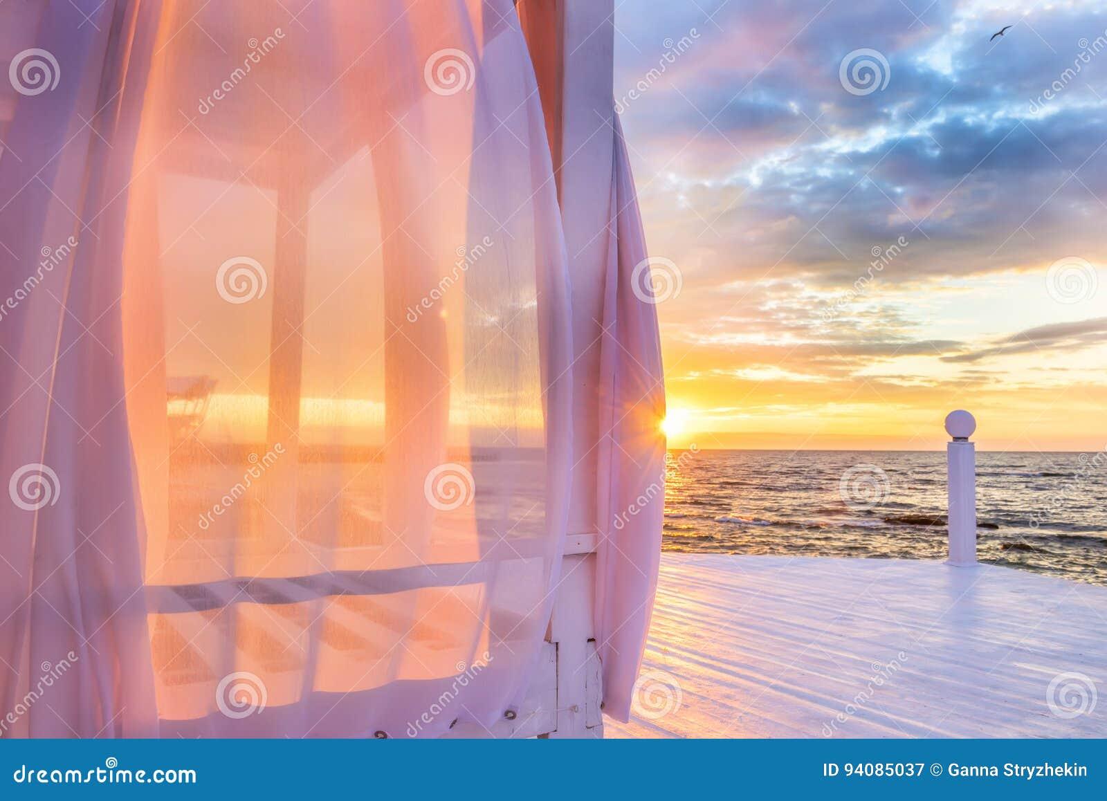 与空中被风吹桃红色帷幕的一个眺望台在海滨在黎明