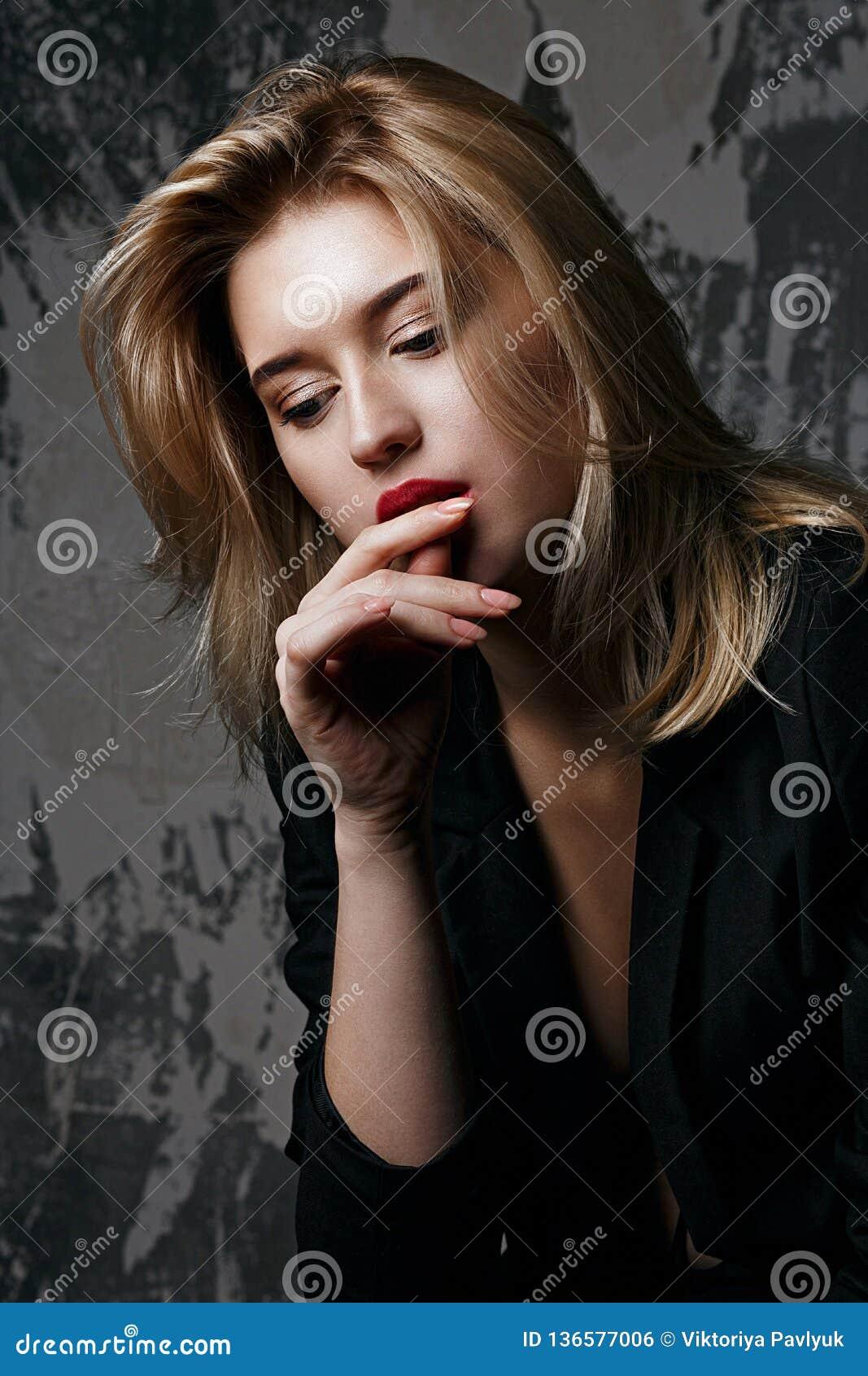 与穿黑夹克的完善的皮肤的魅力白肤金发的模型摆在有阴影的演播室