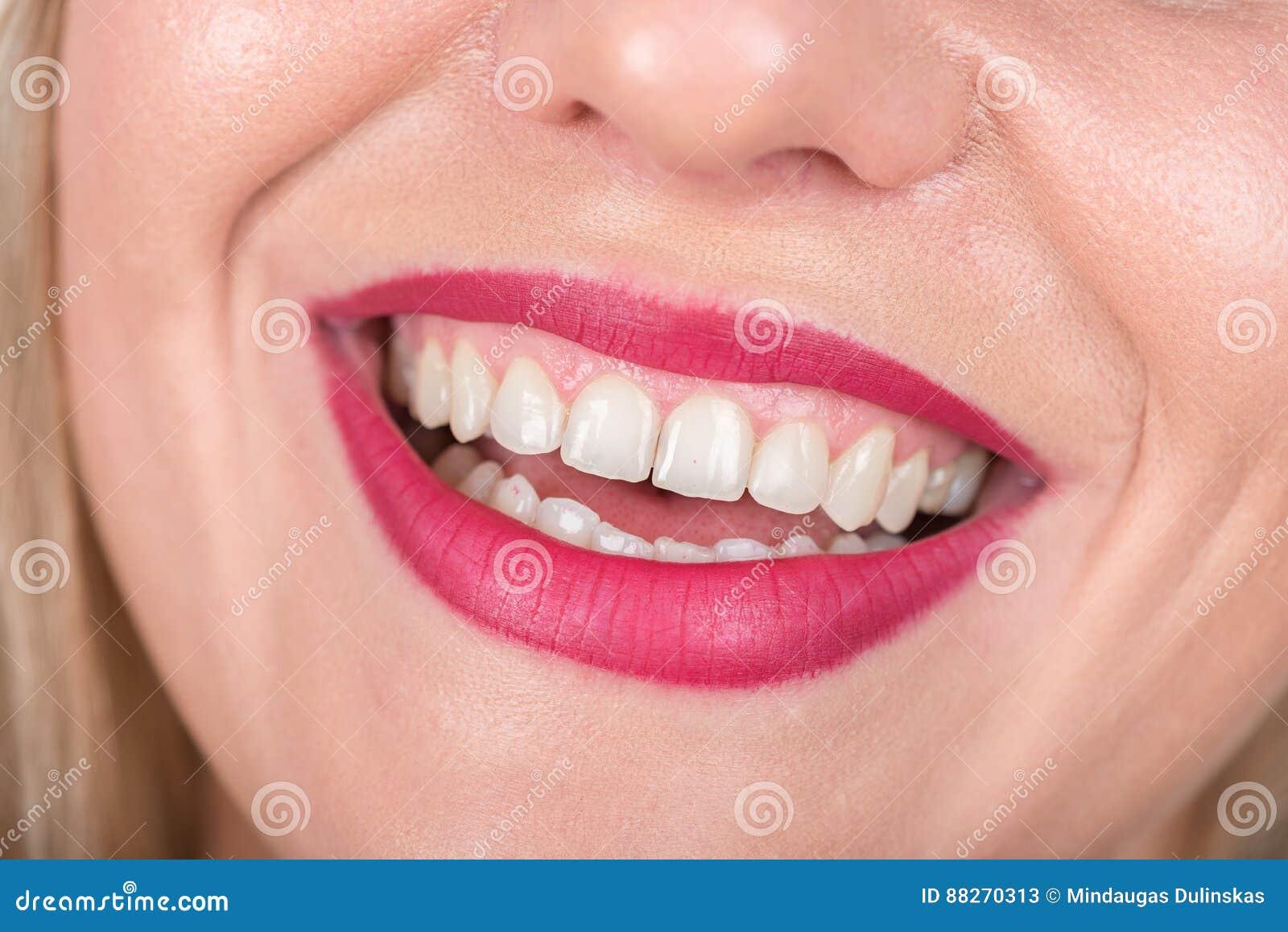 与笑的妇女面孔 白色牙和红色唇膏在使用中 演播室照片写真