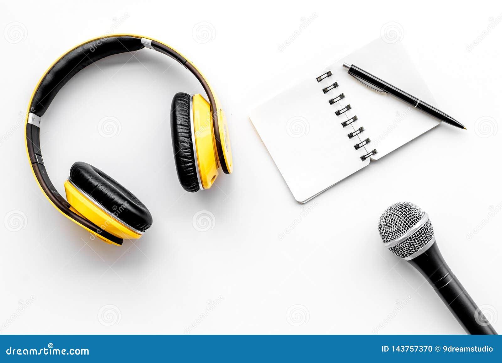 与笔记本、话筒和耳机的播客纪录在文本的白色背景顶视图空间