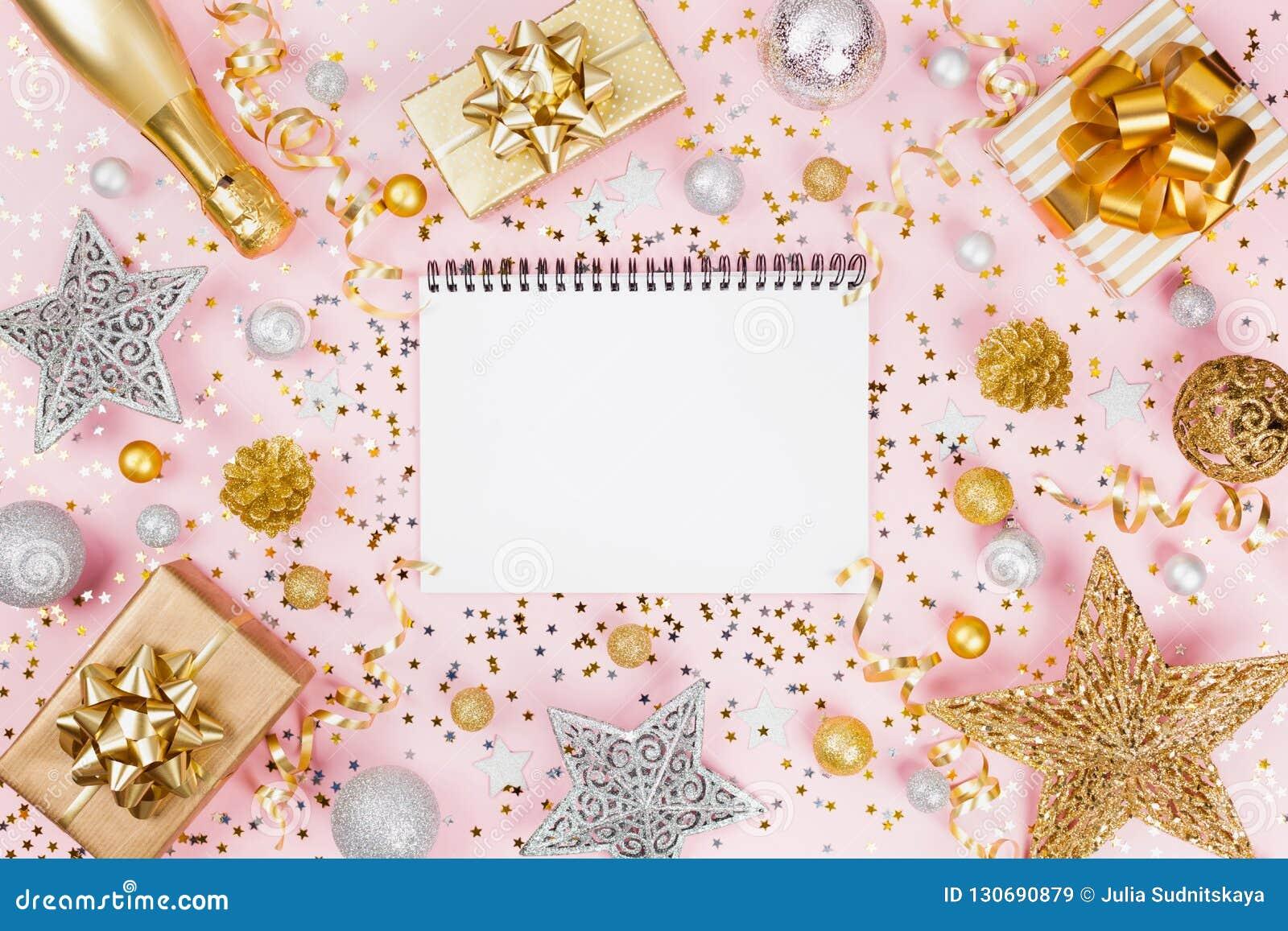 与笔记本的圣诞节背景、礼物或者当前箱子、香槟、五彩纸屑和装饰在桃红色台式视图 平的位置