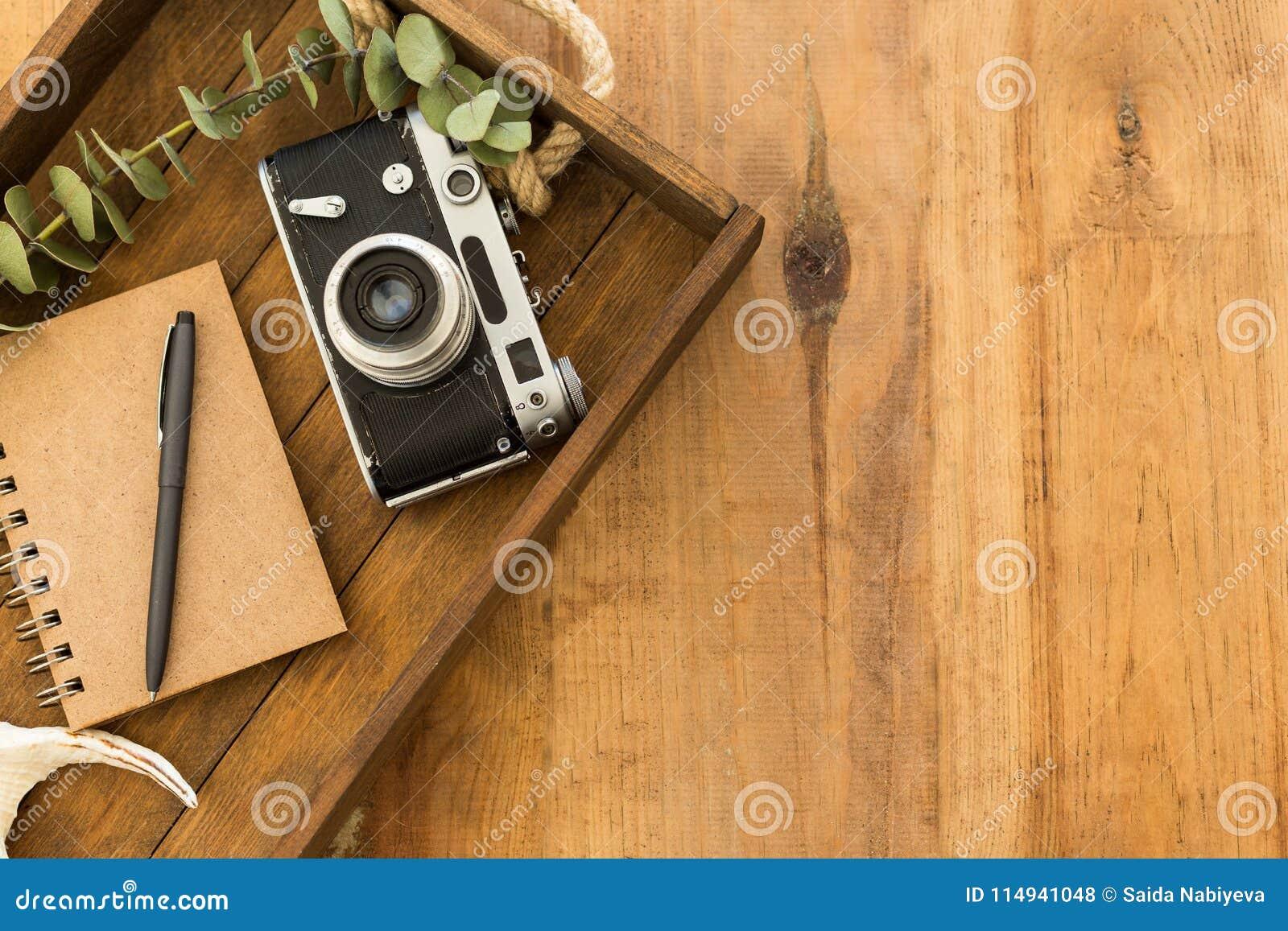 与笔记薄、黑笔和葡萄酒照相机的平的位置