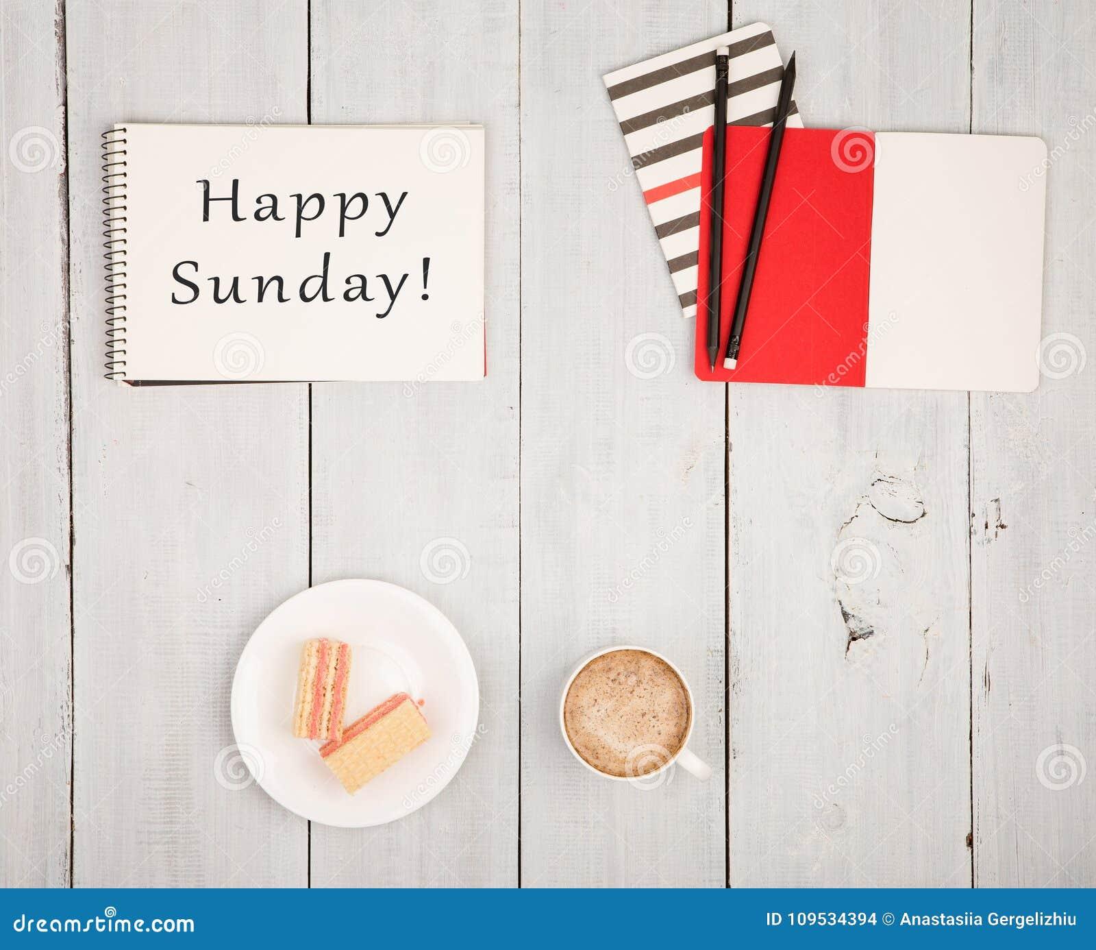 与笔记薄的办公室桌和文本& x22; 愉快的星期天! & x22; 咖啡和奶蛋烘饼