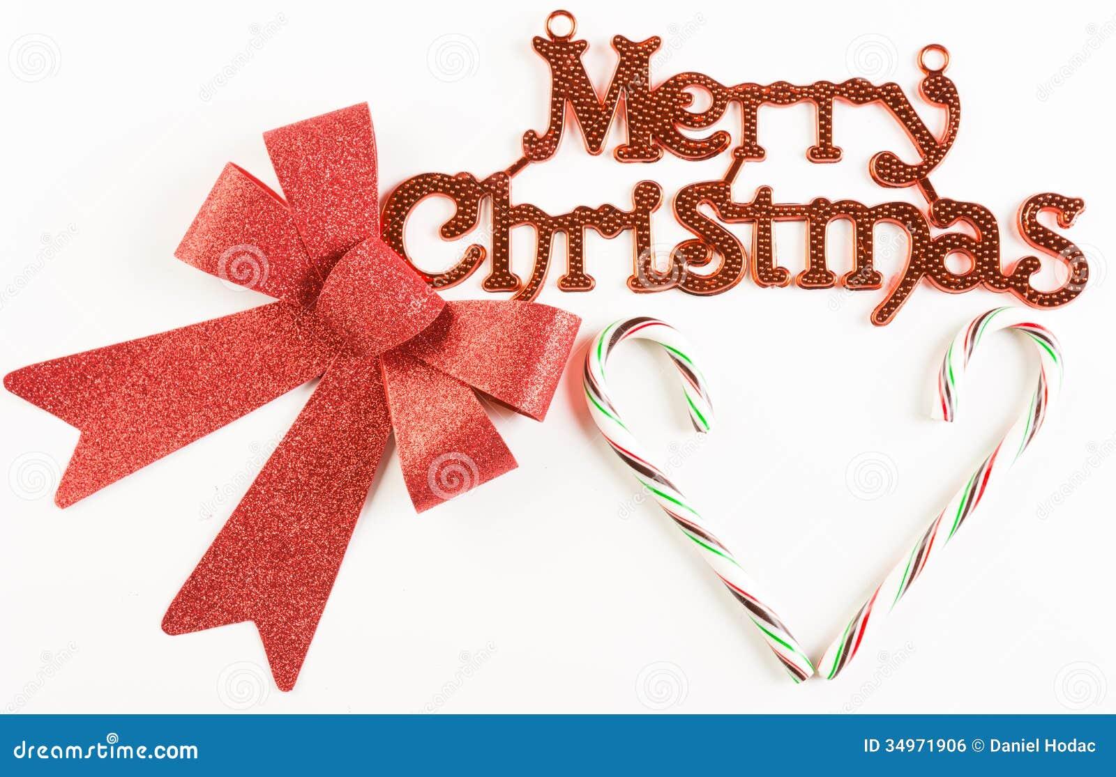 与红色弓的圣诞快乐标志和在白色背景的心形的棒棒糖.图片