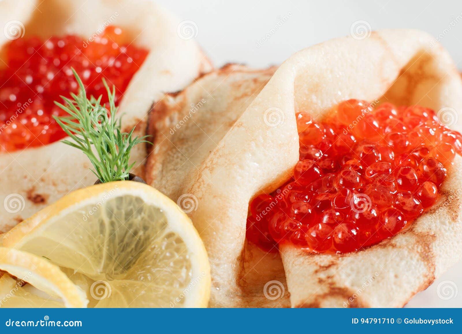 与红色鱼子酱特写镜头的纤巧薄煎饼