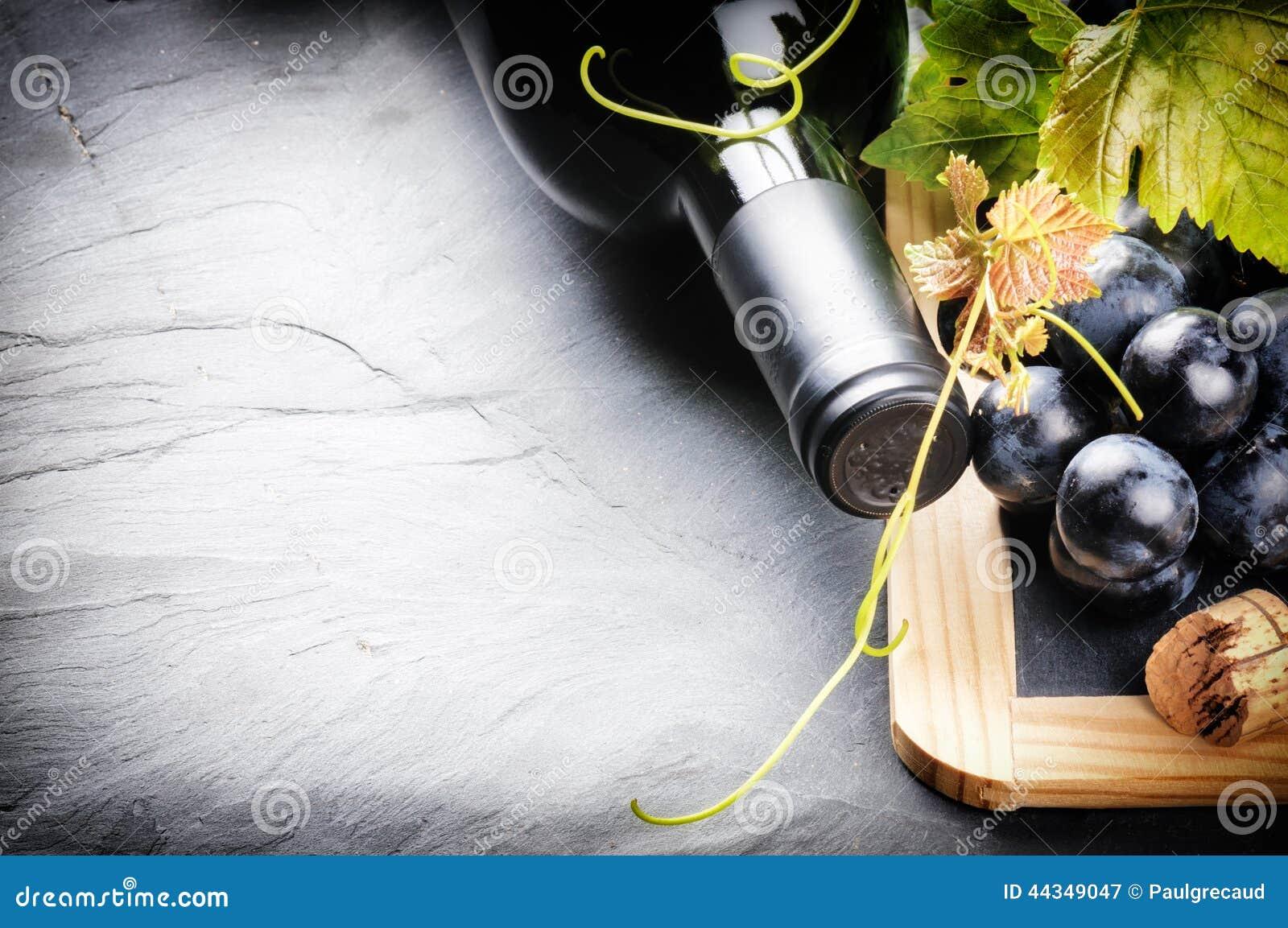 与红葡萄酒瓶和新鲜的葡萄的框架