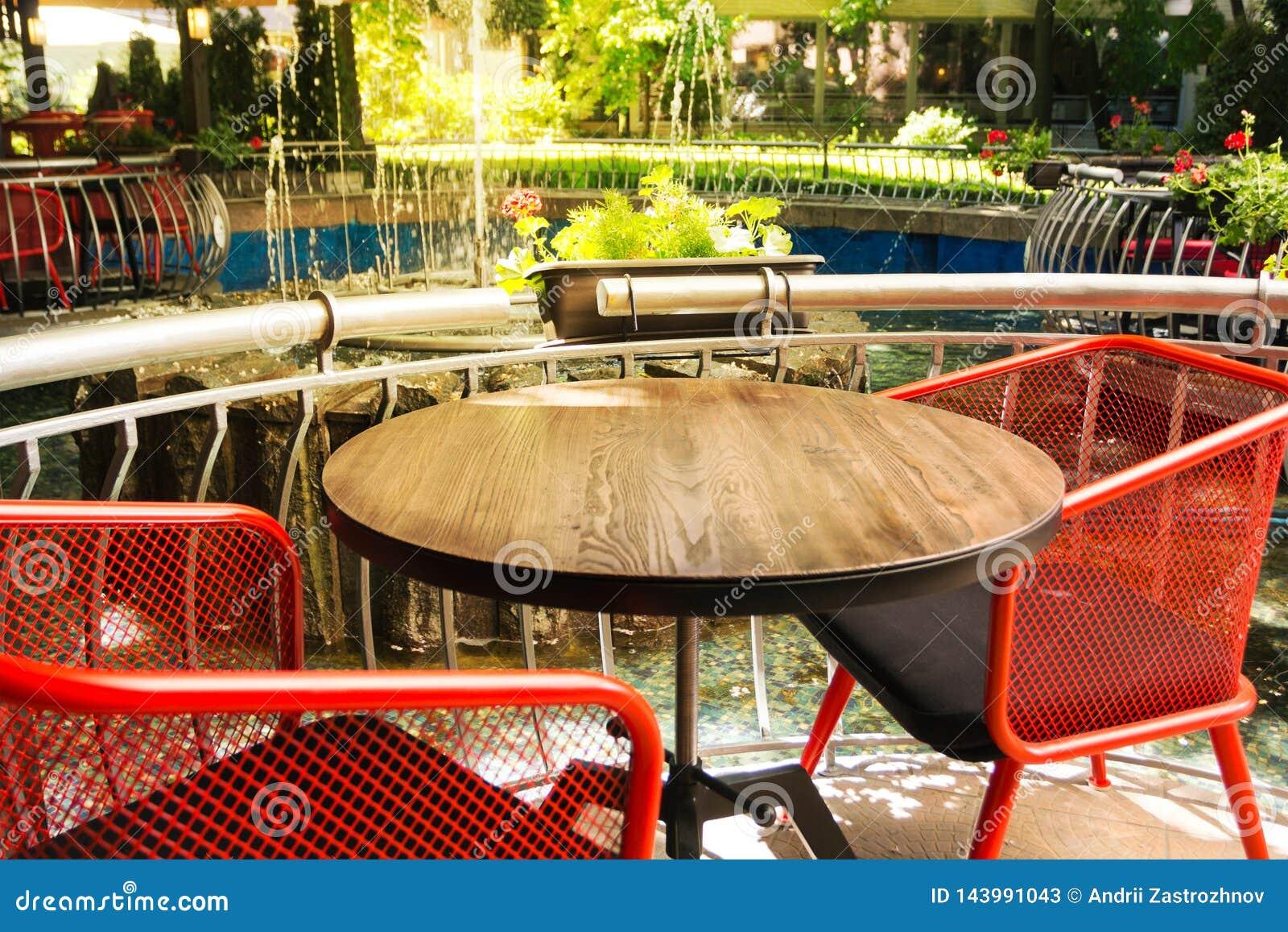 与纹理的空的木桌,与在被弄脏的背景前面的红色椅子 与花、植物和a的一个清淡的街道咖啡馆