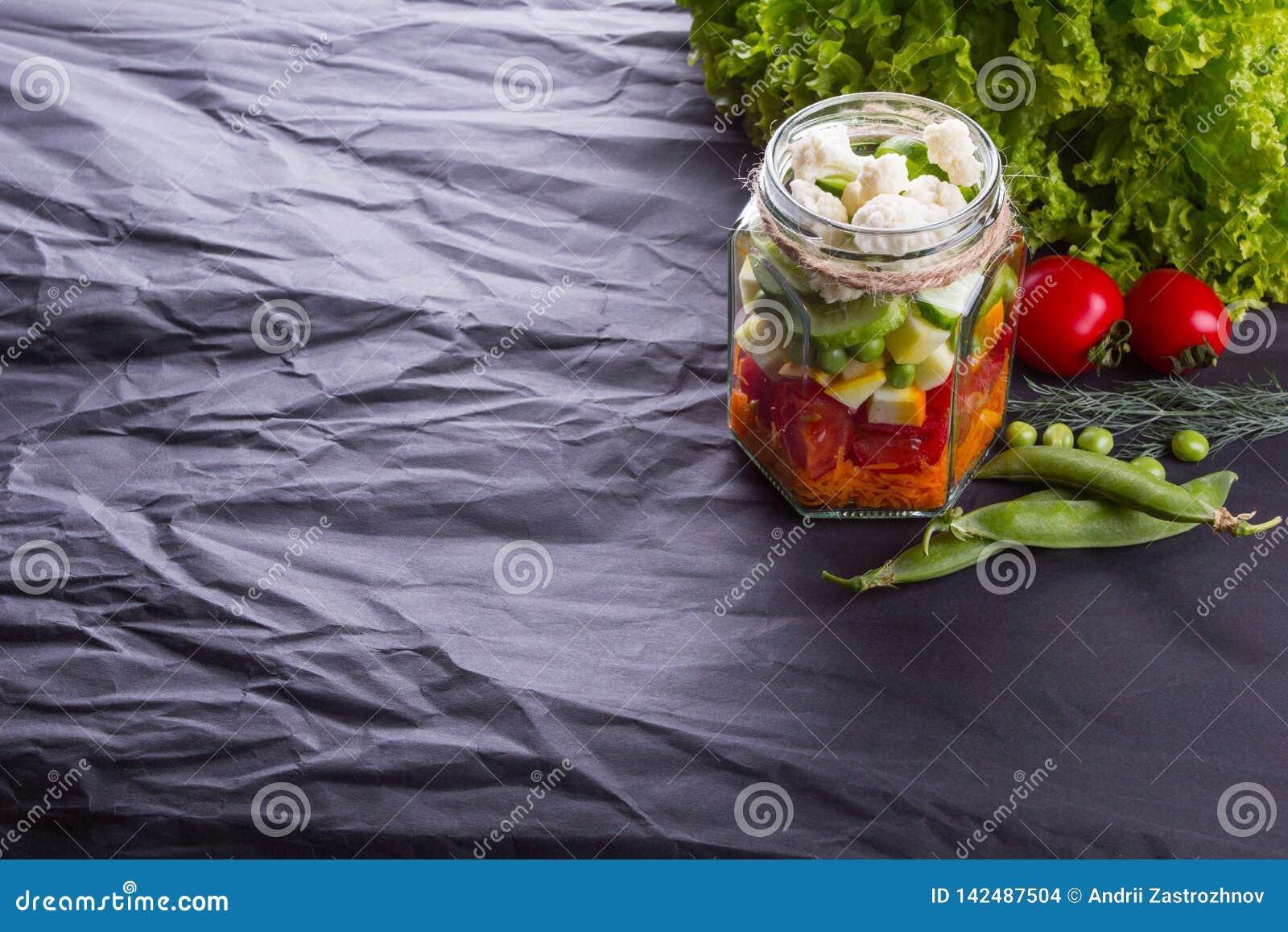 与绿色的新鲜蔬菜沙拉在一个木板的罐,黑织地不很细背景 文本的空间 健康的食物