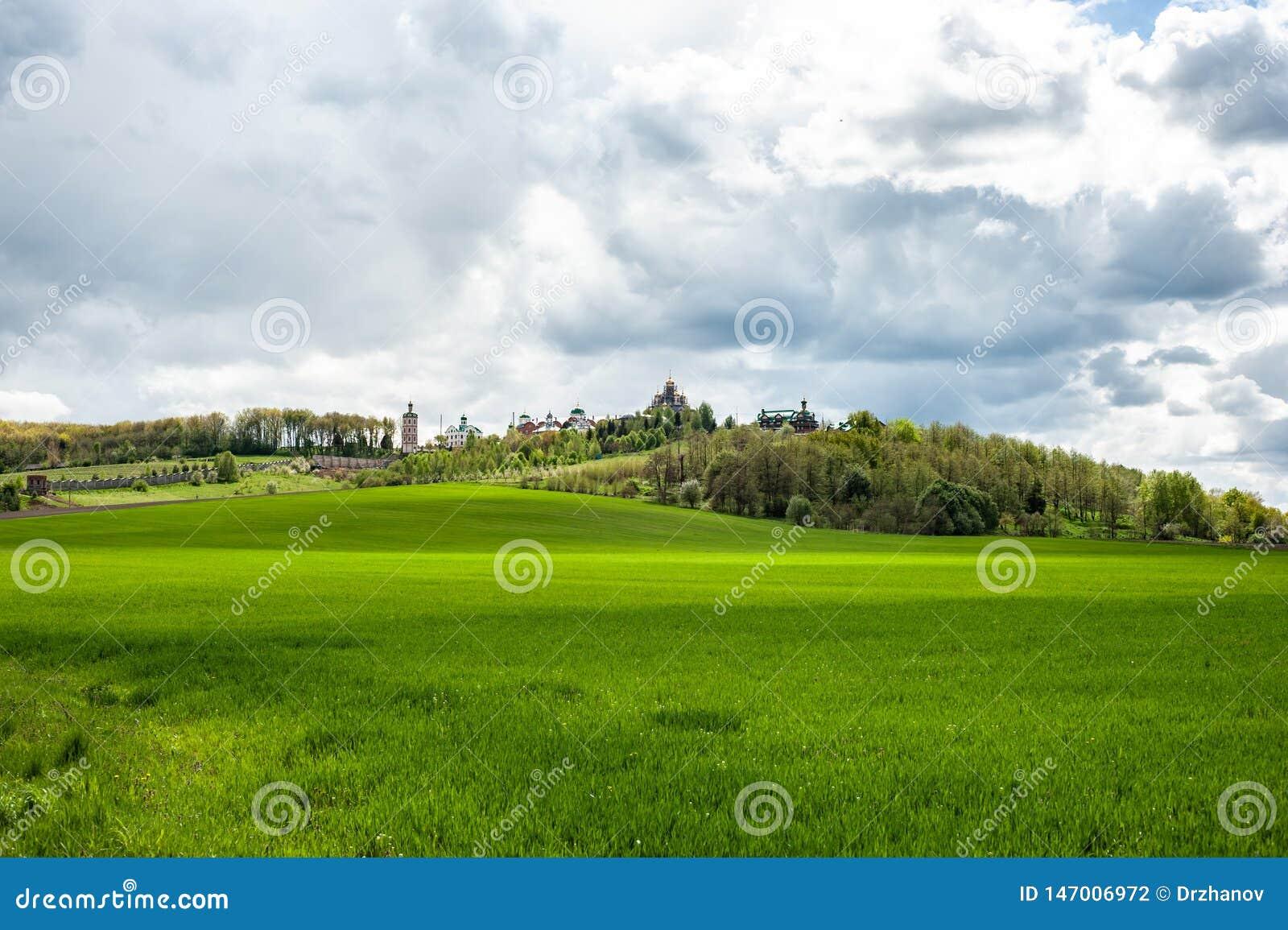 与绿草、树和修道院的风景小山在多云天空下