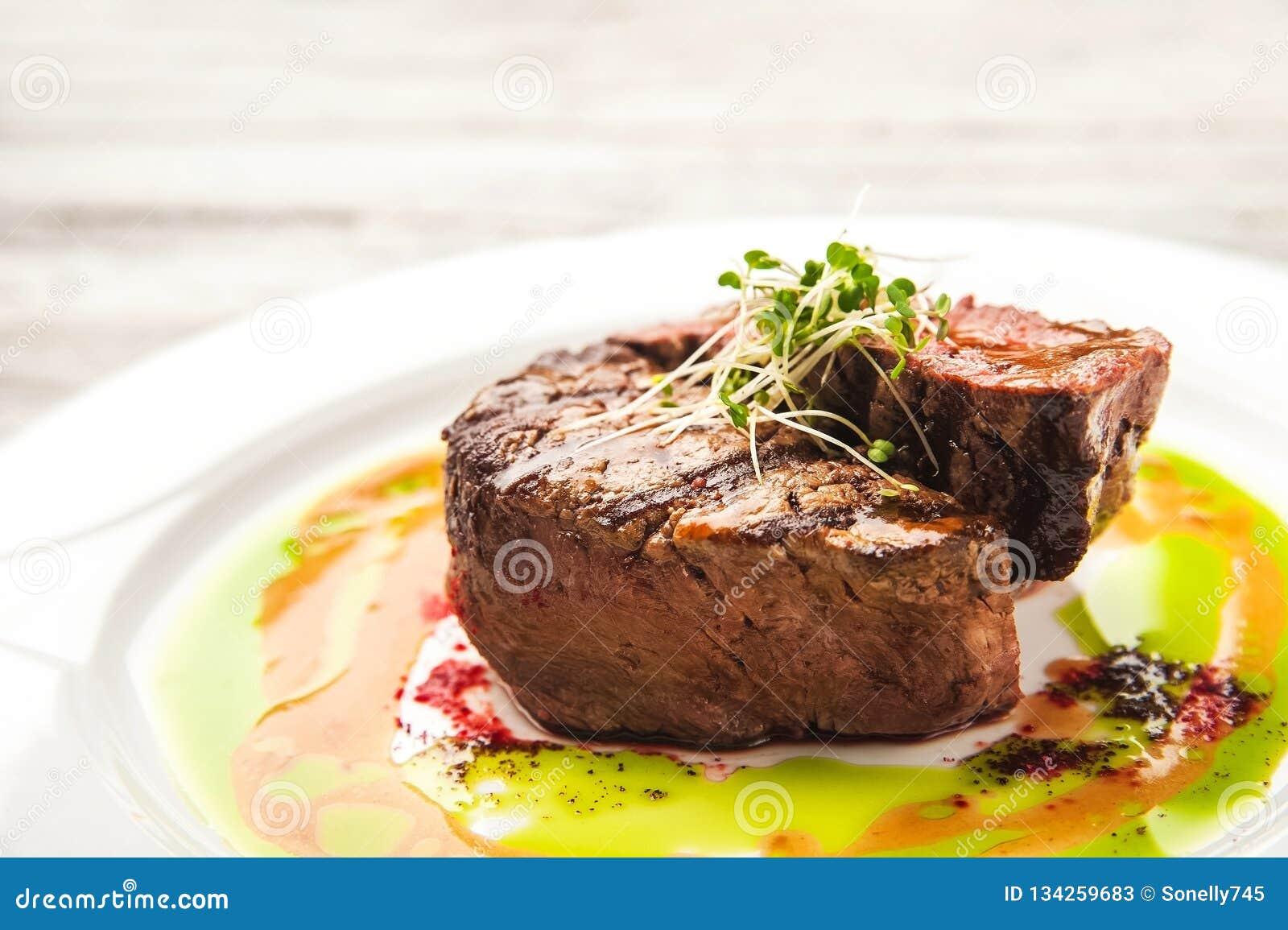 与罕见的程度的烤肉烹调,中等,很好做 关闭牛肉在调味汁和新芽的猪肉牛排