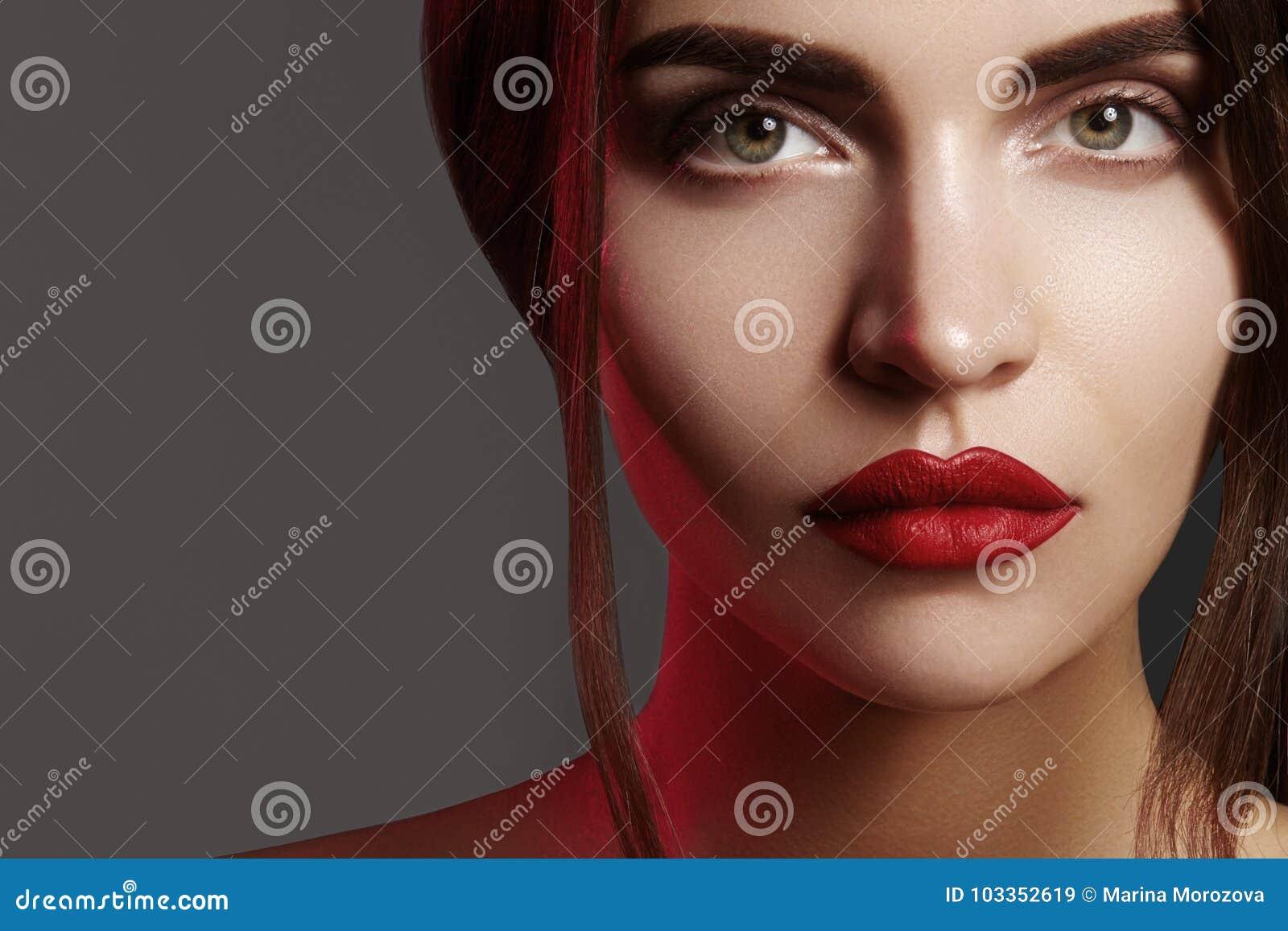 与美丽的妇女面孔的特写镜头画象 时尚嘴唇构成、干净的发光的皮肤和强的眼眉的红颜色