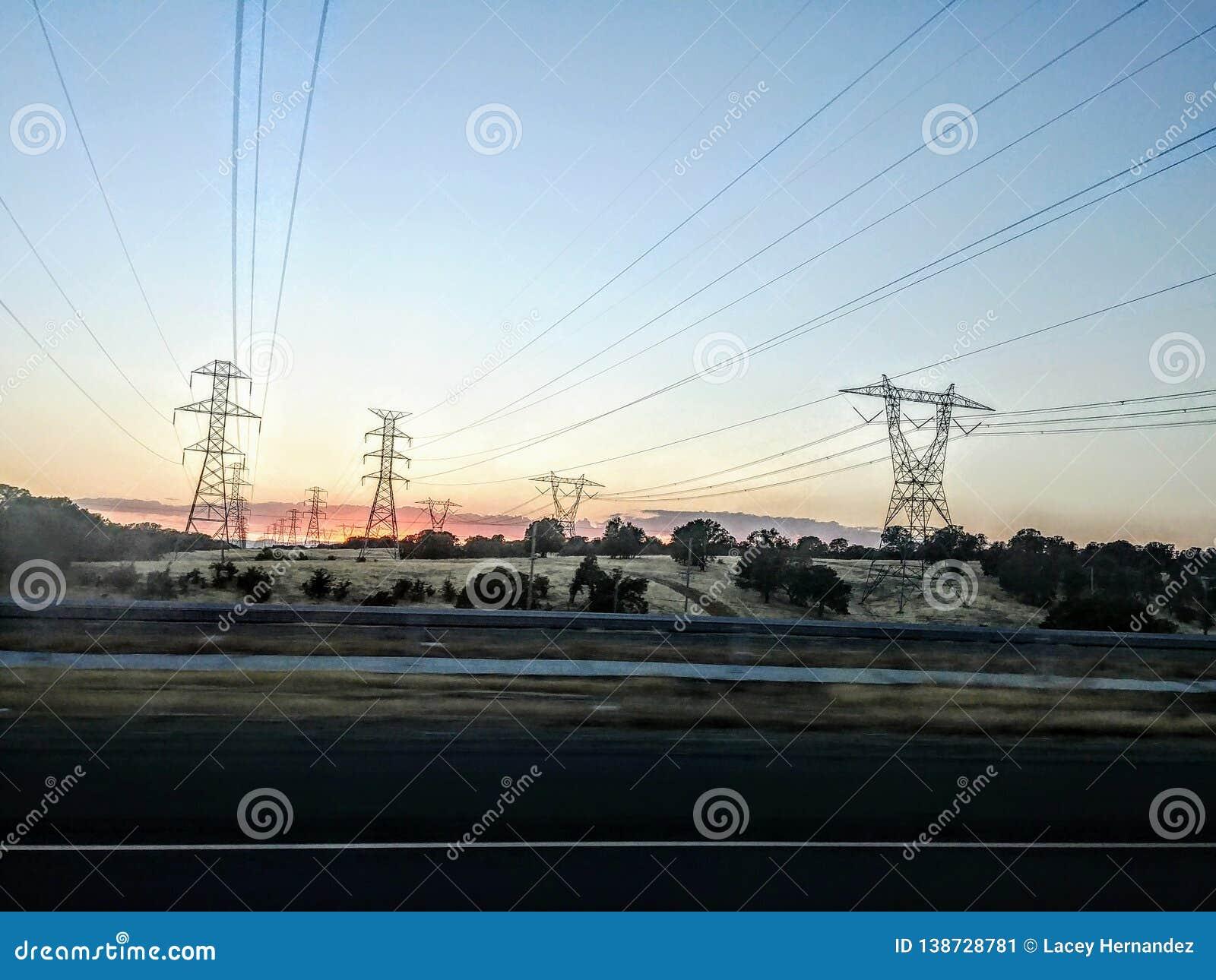 与美丽的小山和输电线的日出