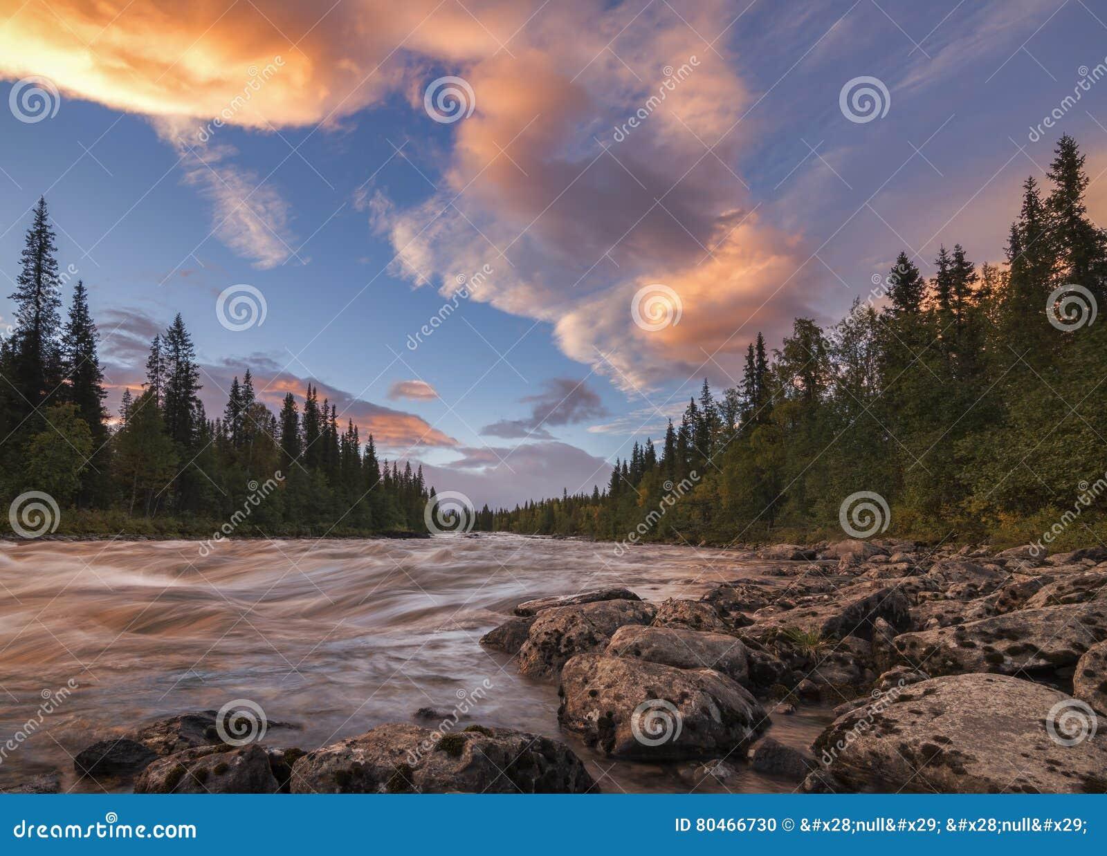 与美丽的橙色云彩的平静和镇静河日落,瑞典