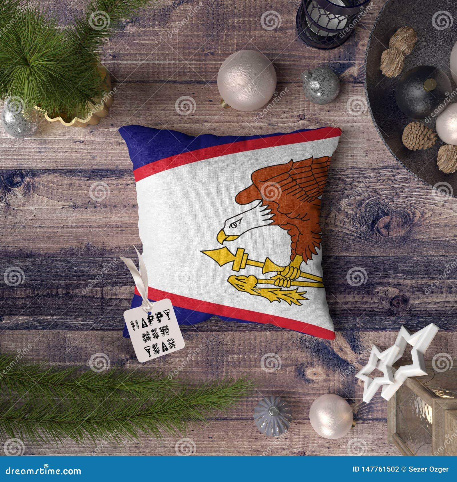 与美属萨摩亚旗子的新年快乐标记在枕头 在木桌上的圣诞装饰概念与可爱的对象