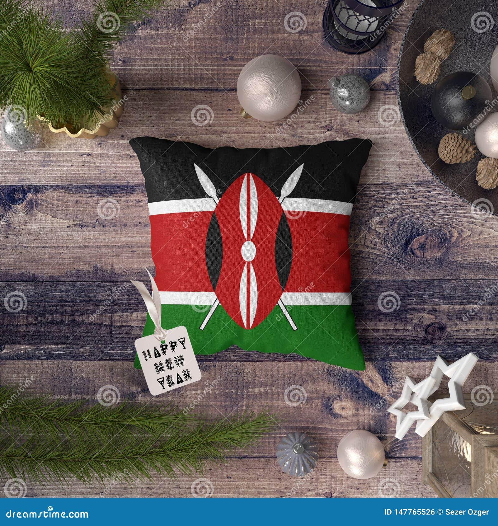 与肯尼亚旗子的新年快乐标记在枕头 在木桌上的圣诞装饰概念与可爱的对象