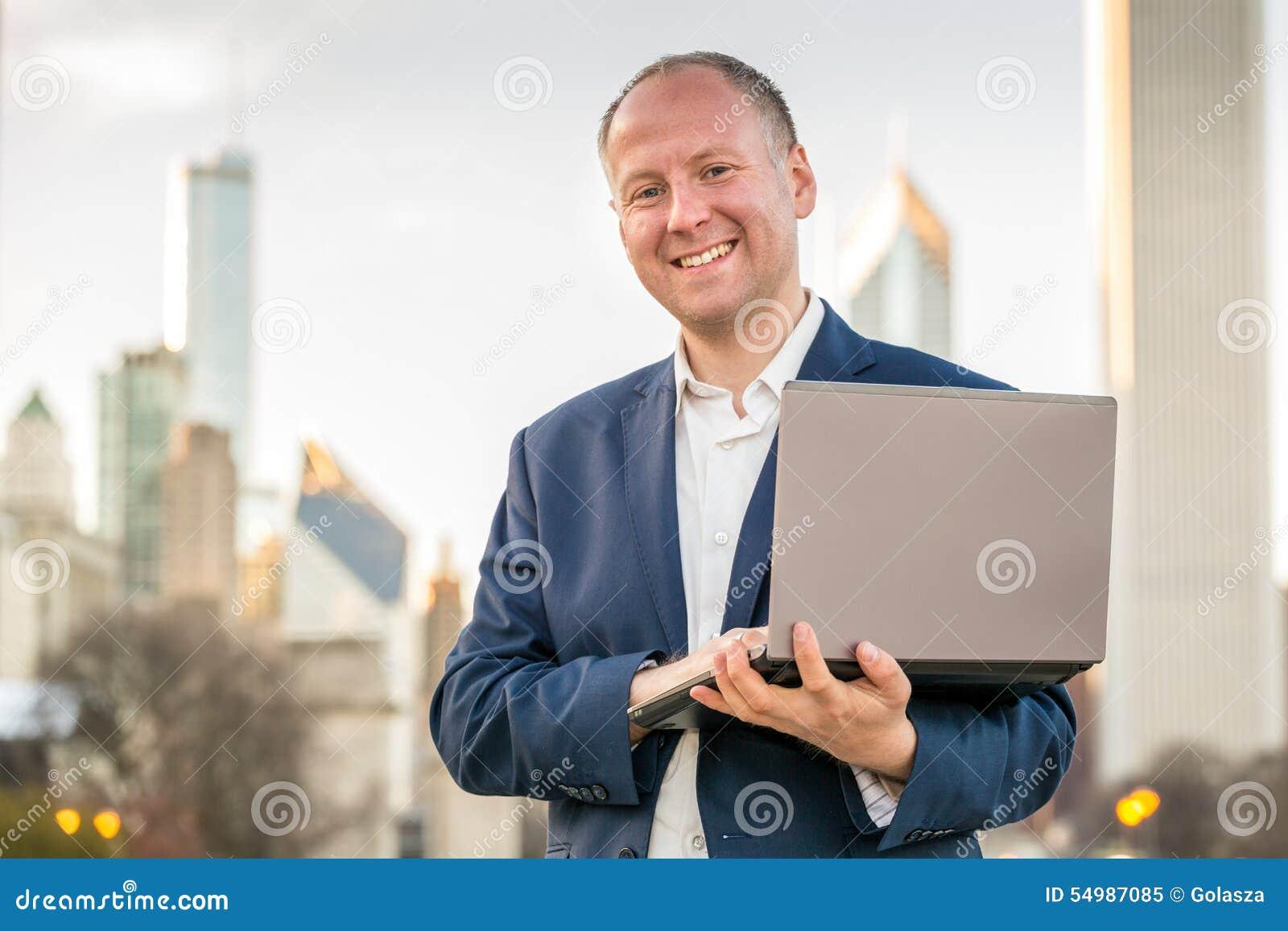 与膝上型计算机的商人在办公楼前面