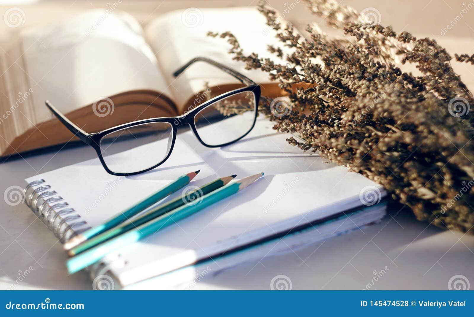 与花、书、玻璃和书写用具的静物画