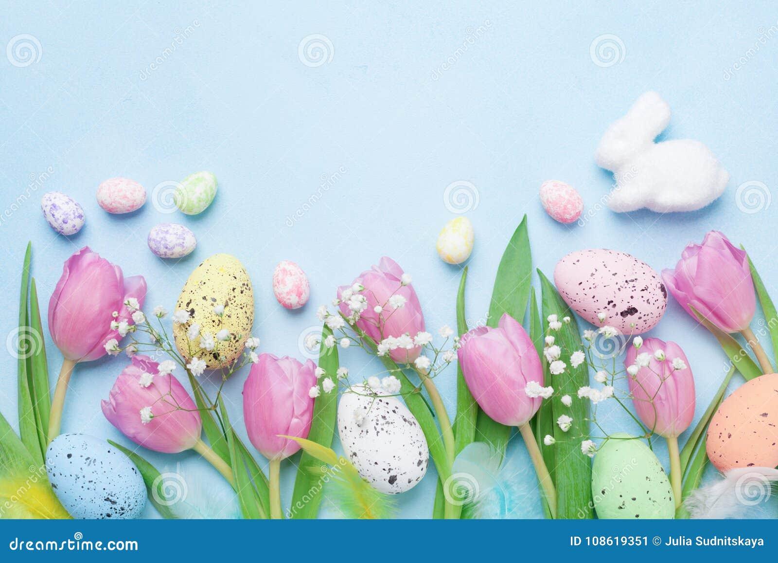 与花、兔宝宝、五颜六色的鸡蛋和羽毛的春天背景在蓝色台式视图 看板卡愉快的复活节