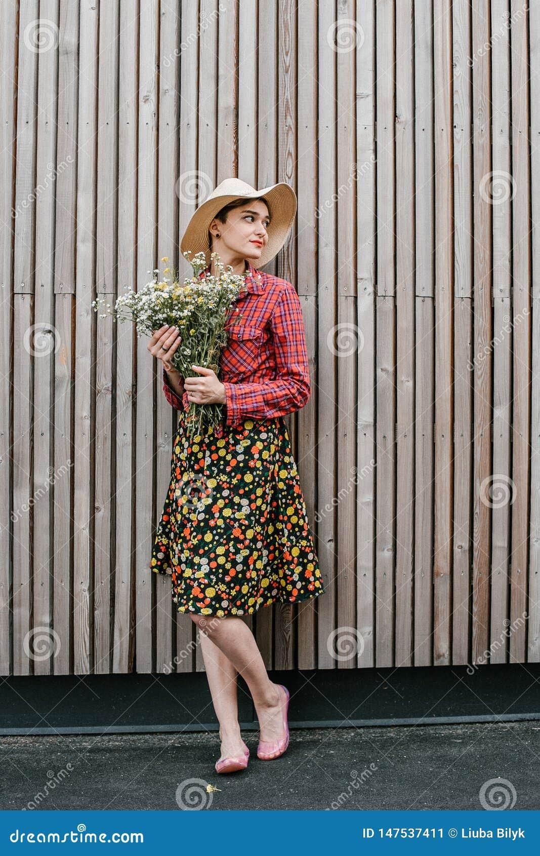 与花的时髦的女孩身分 在木墙壁附近的美女 春天样式 夏天步行 r ?treadled