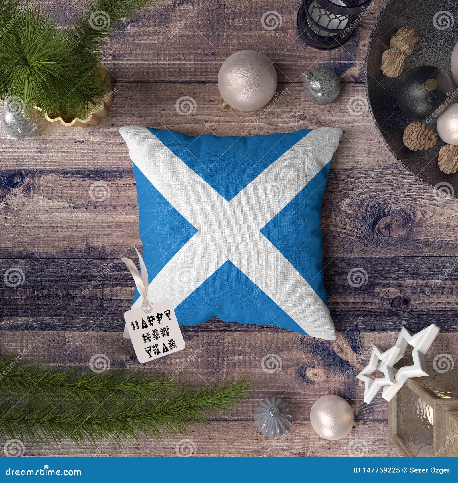 与苏格兰旗子的新年快乐标记在枕头 在木桌上的圣诞装饰概念与可爱的对象