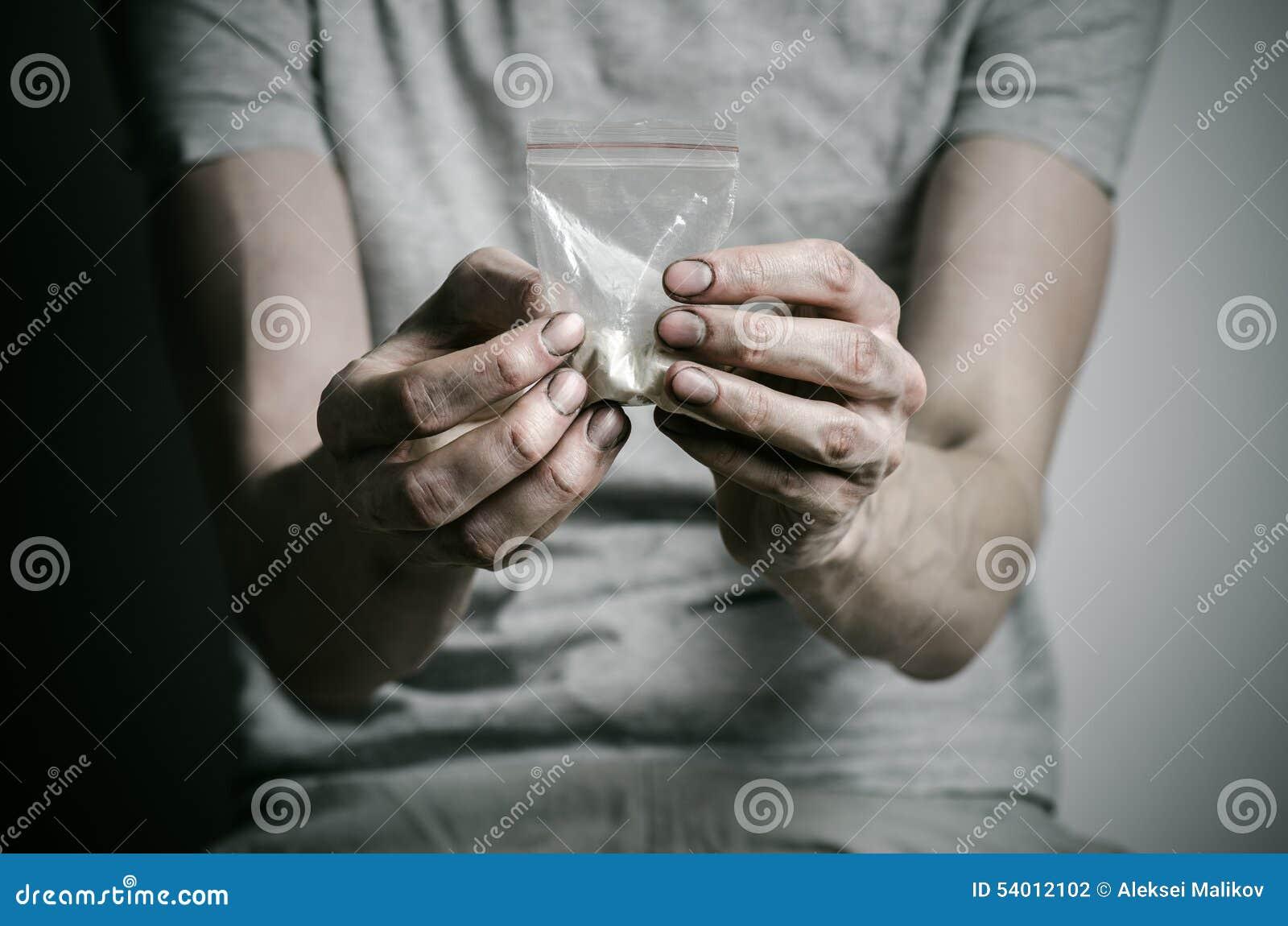 与药物和毒瘾题目的战斗:使拿着可卡因包裹上瘾在一件灰色T恤杉的在的黑暗的背景