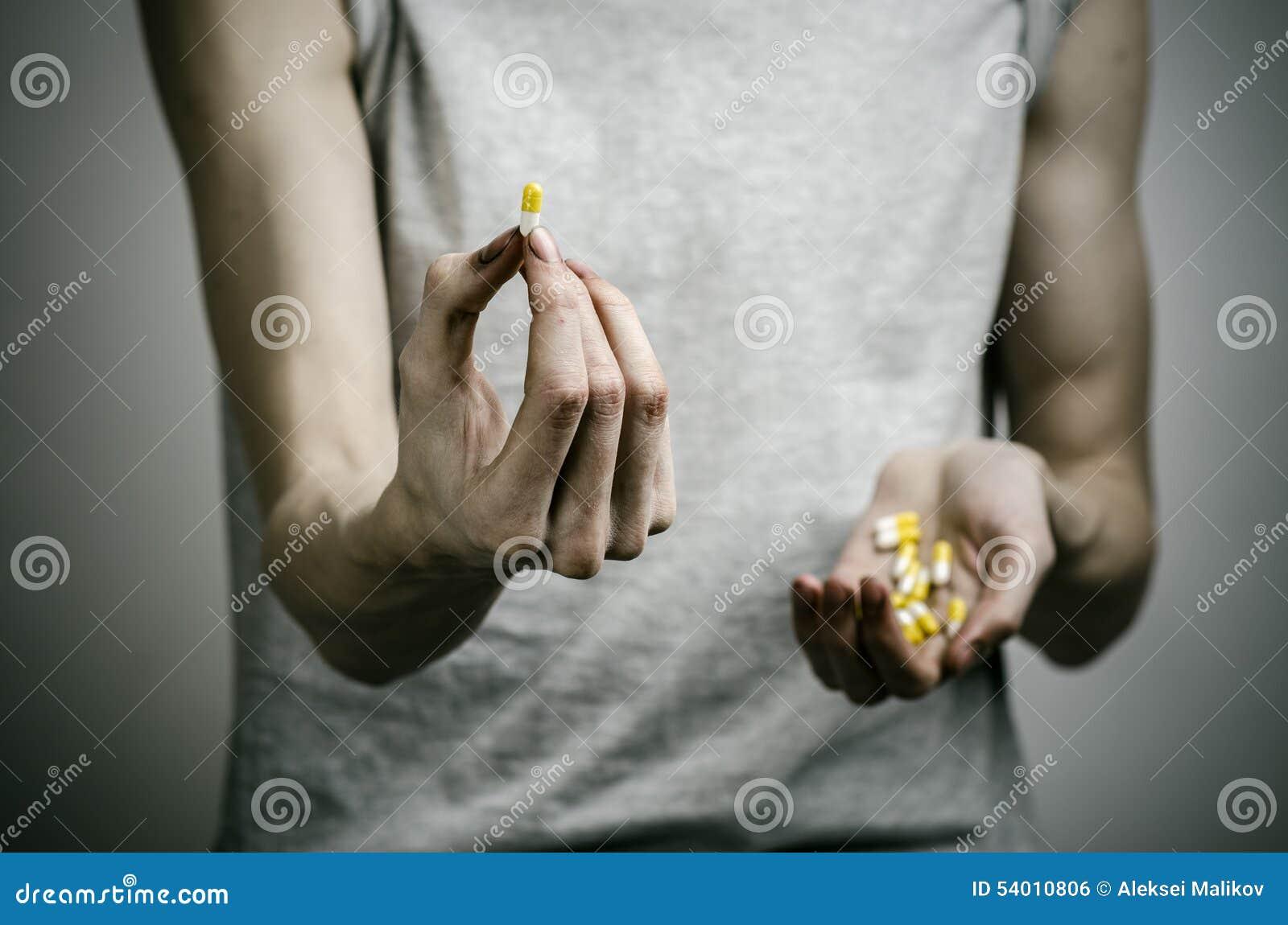 与药物和毒瘾题目的战斗:使拿着在黑暗的背景的麻醉药片上瘾