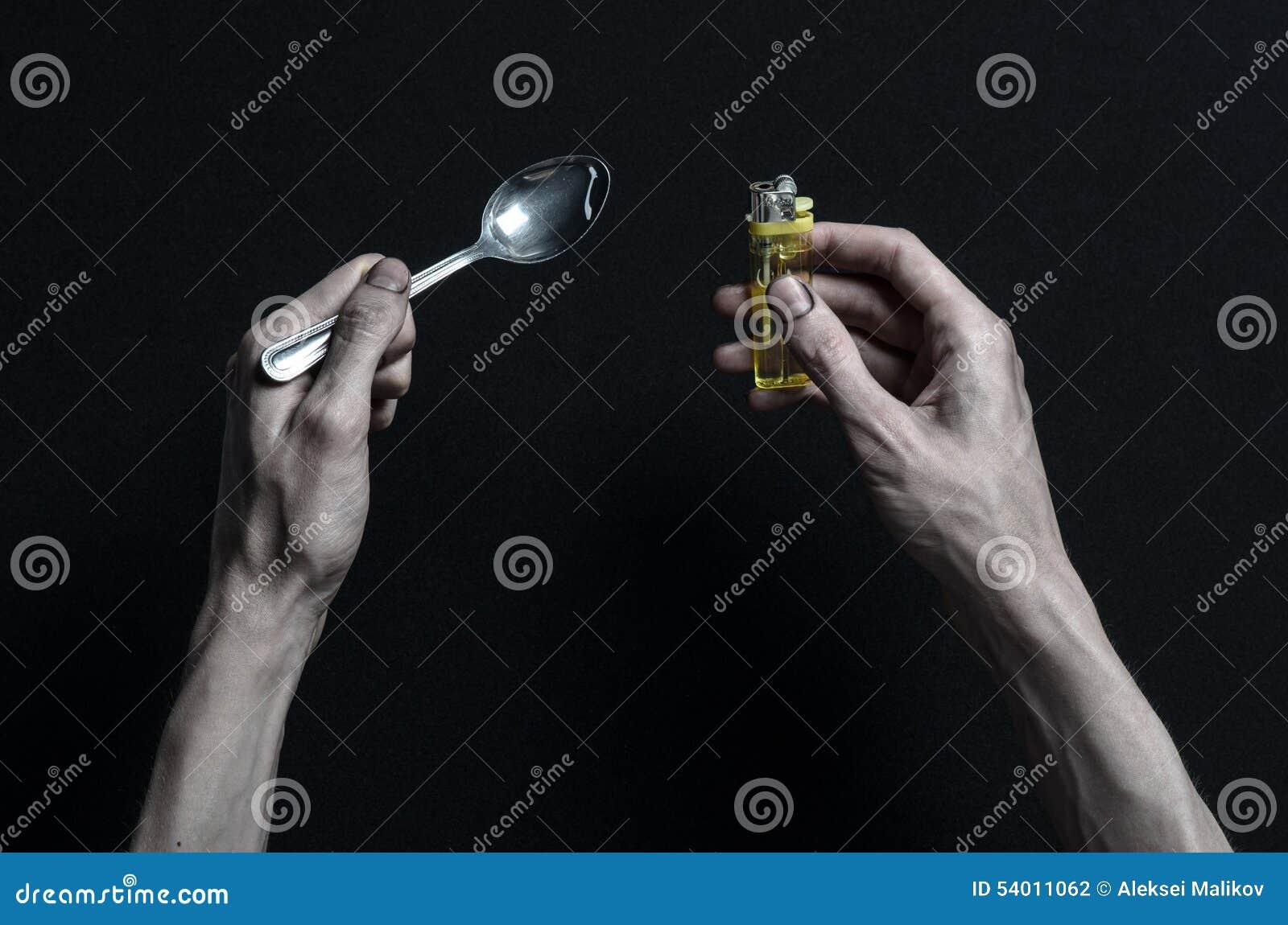 与药物和毒瘾题目的战斗:手上瘾者谎言在一张黑暗的桌上和在它附近是药物,顶面演播室