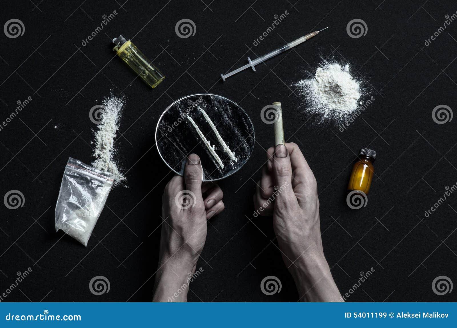 与药物和毒瘾题目的战斗:手上瘾者谎言在一张黑暗的桌上和在它附近是药物