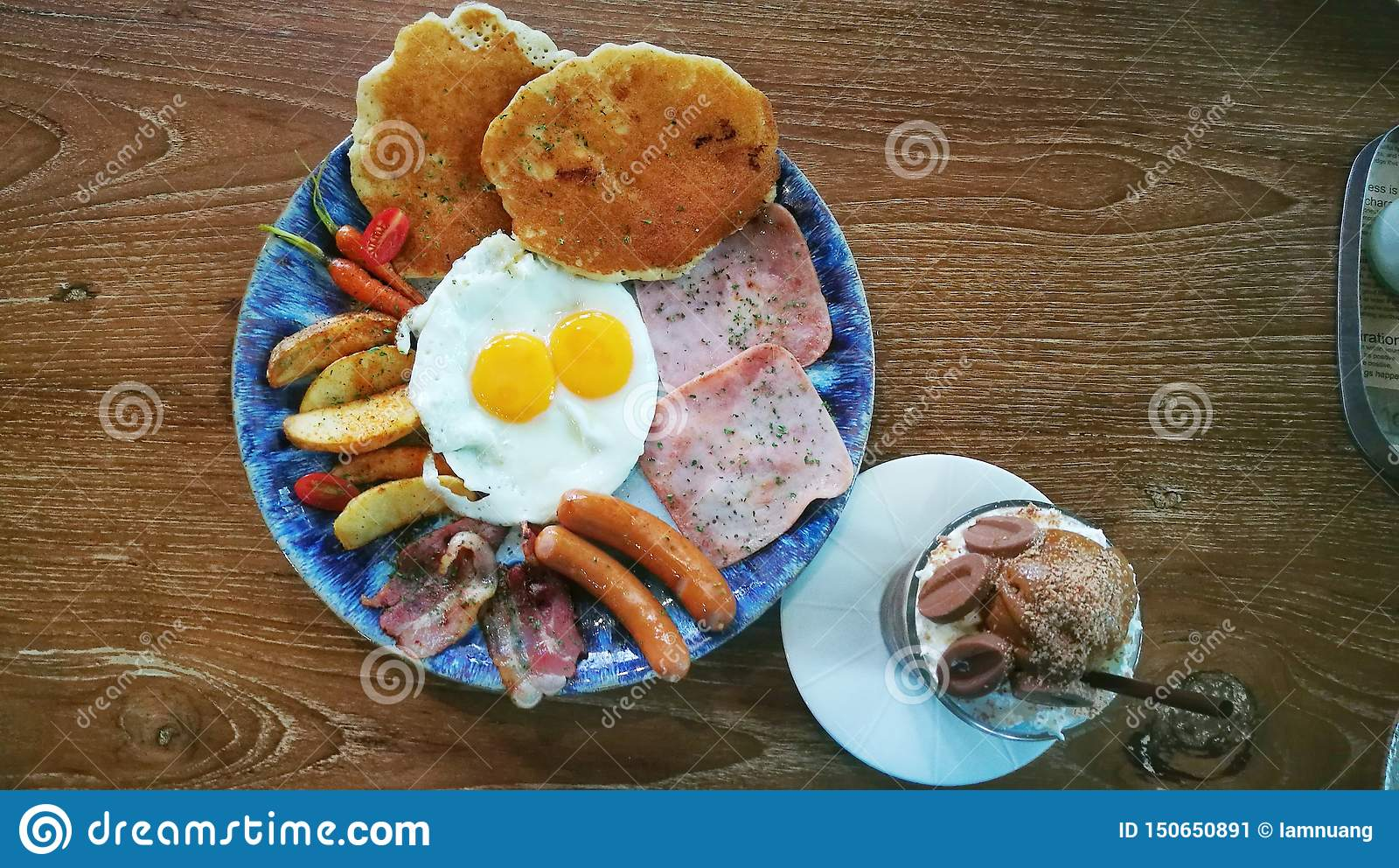 与荷包蛋、火腿、香肠、烟肉、嫩胡萝卜、被烘烤的土豆和被冰的巧克力的生气勃勃早餐在木桌上