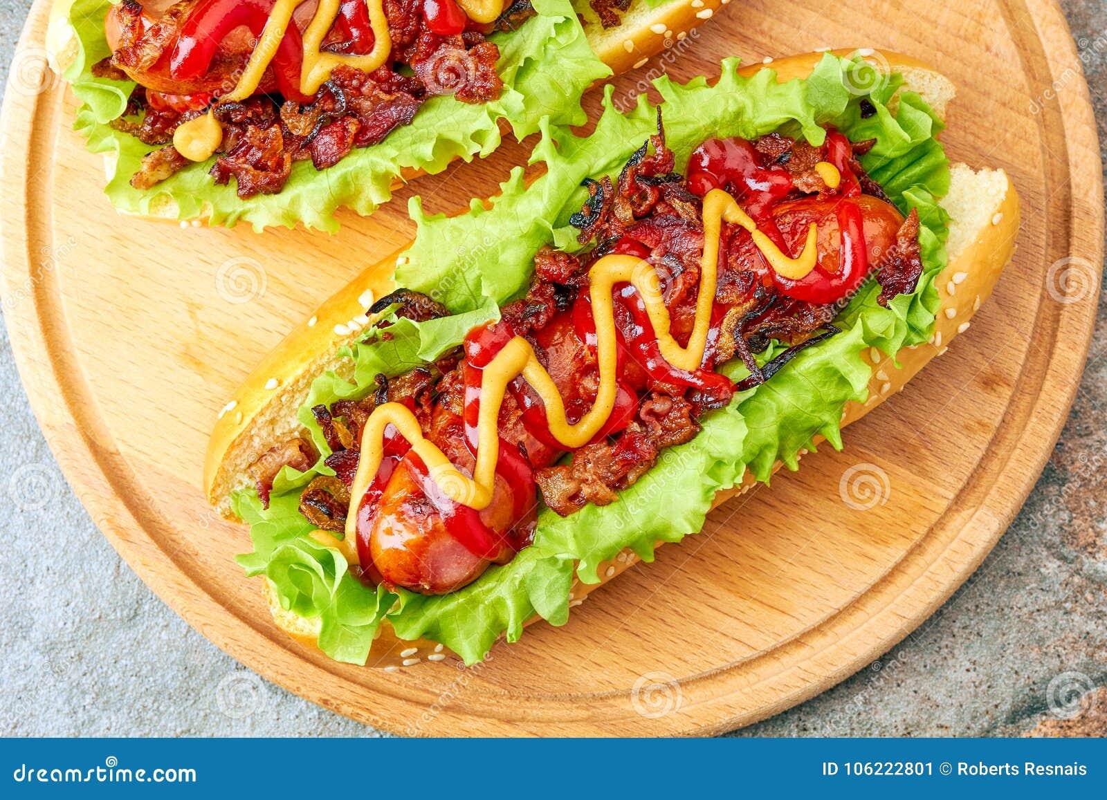 与莴苣、烟肉和葱顶部的两个自创热狗