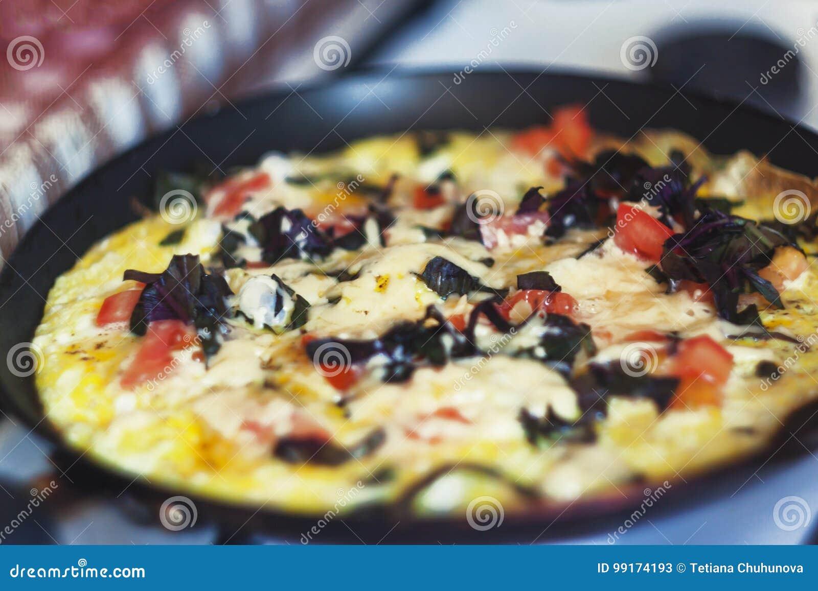 与菜的煎蛋卷在火炉的一个煎锅