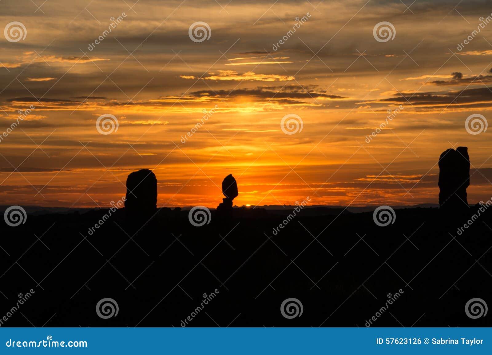 与落日射线的平衡的岩石日落风景